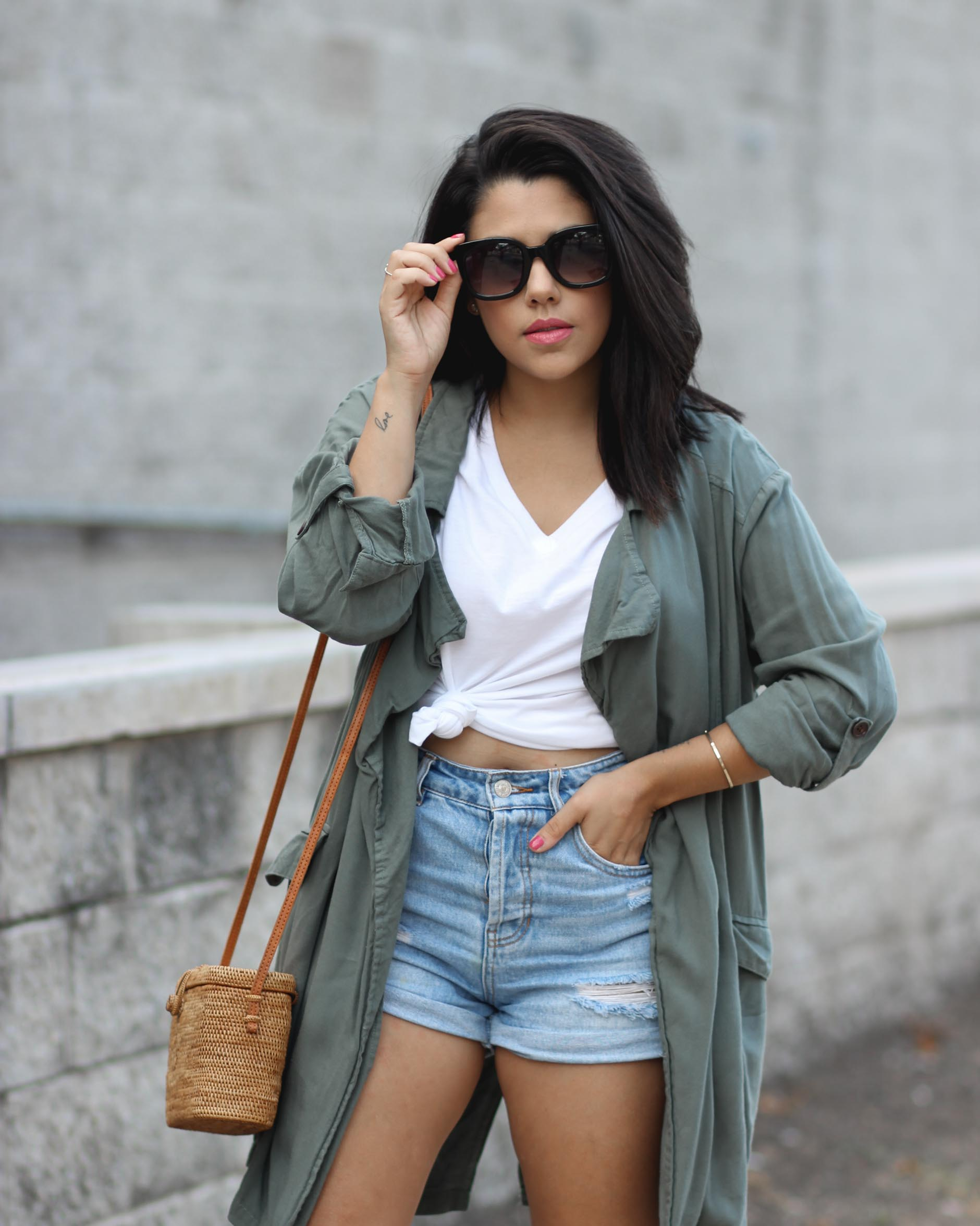 lifestyle blogger naty michele wearing a knotted tee with a trench coat and denim shorts holding her sunglasses