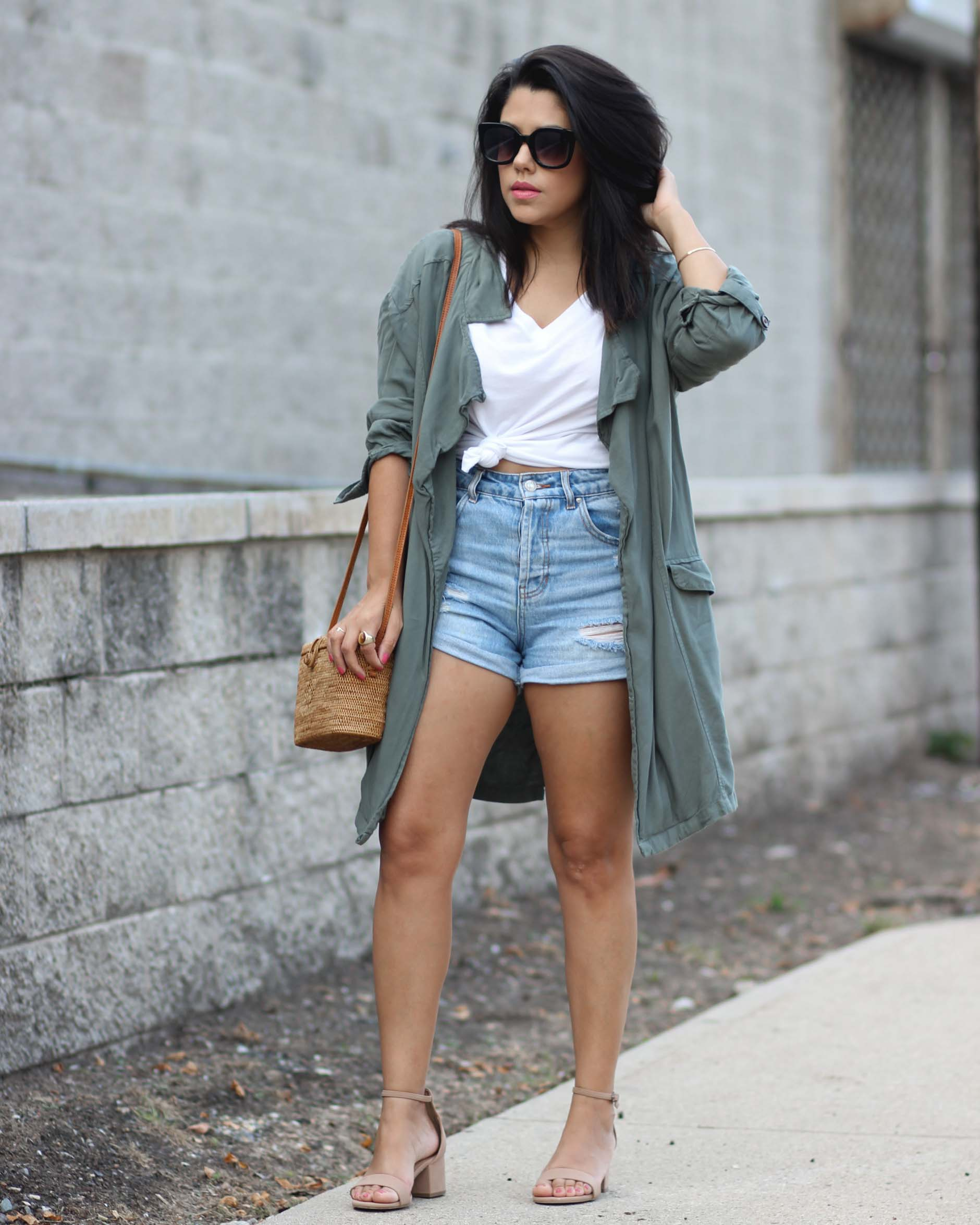 lifestyle blogger naty michele standing in a knotted tee with a trench coat and denim shorts