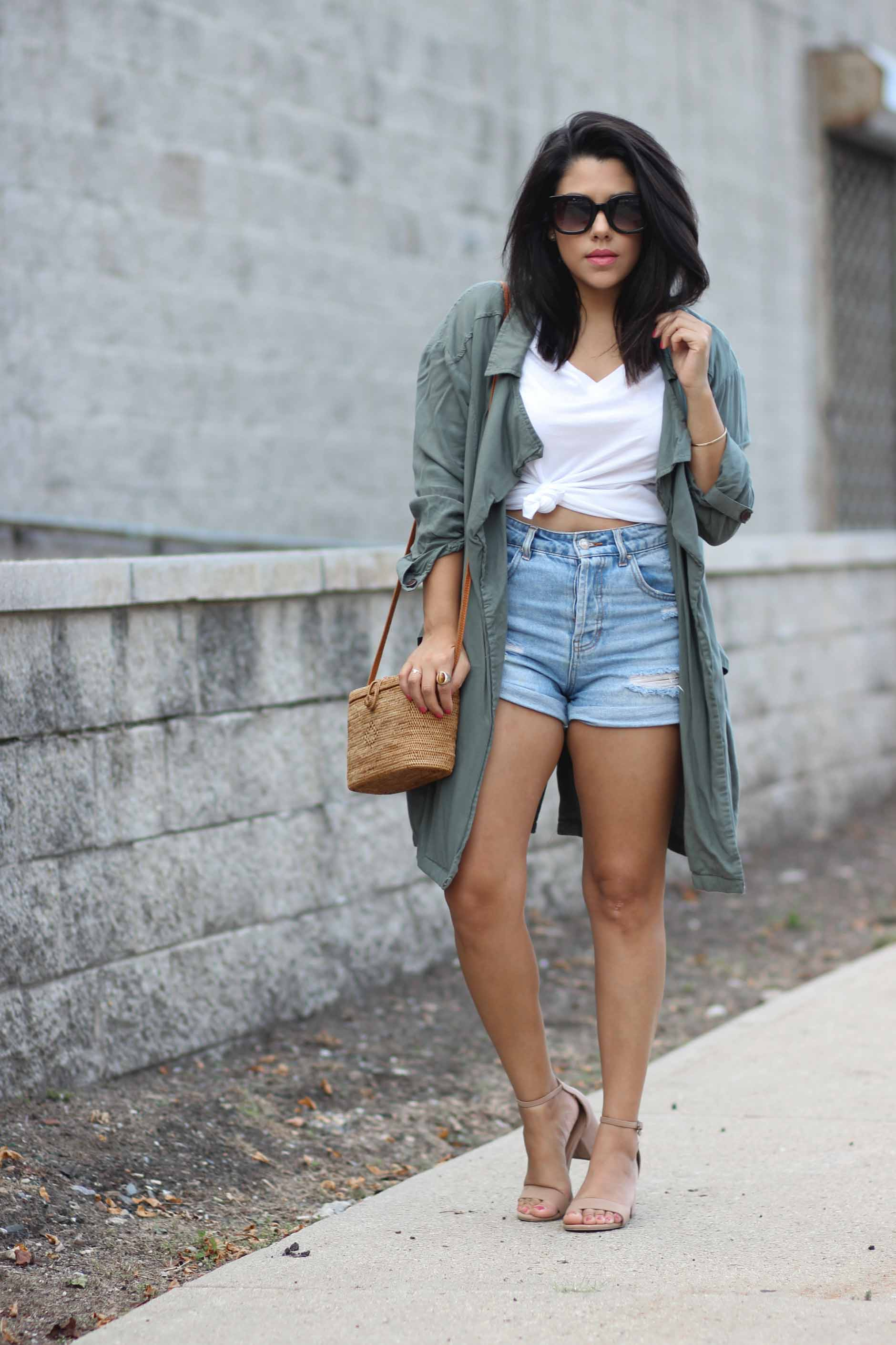 lifestyle blogger naty michele standing in a knotted tee with denim shorts and a draped trench coat