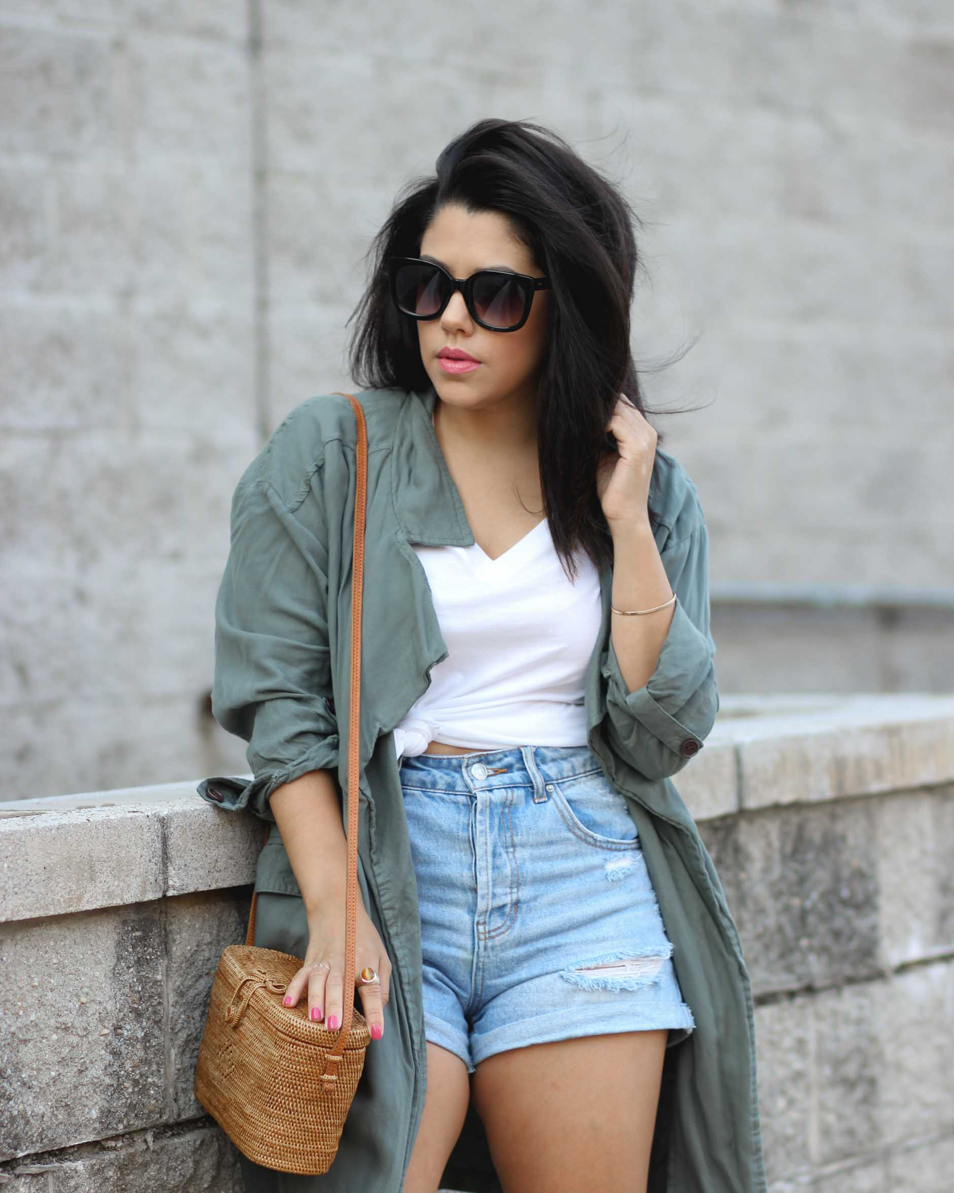 lifestyle blogger naty michele wearing a knotted tee with denim shorts and a draped trench coat