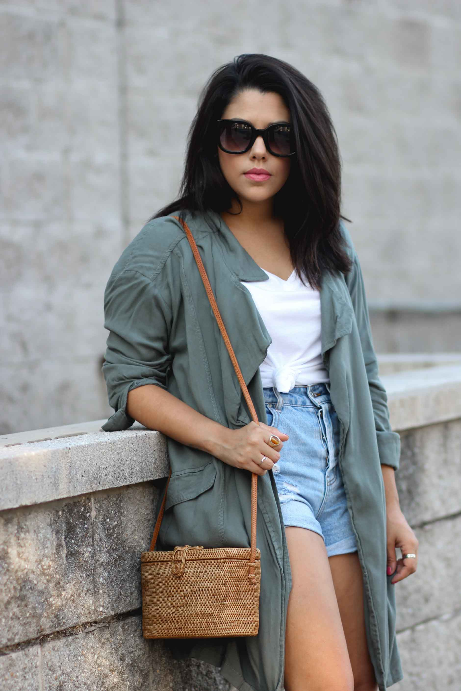 lifestyle blogger naty michele wearing a draped trench coat with a knotted tee and denim shorts