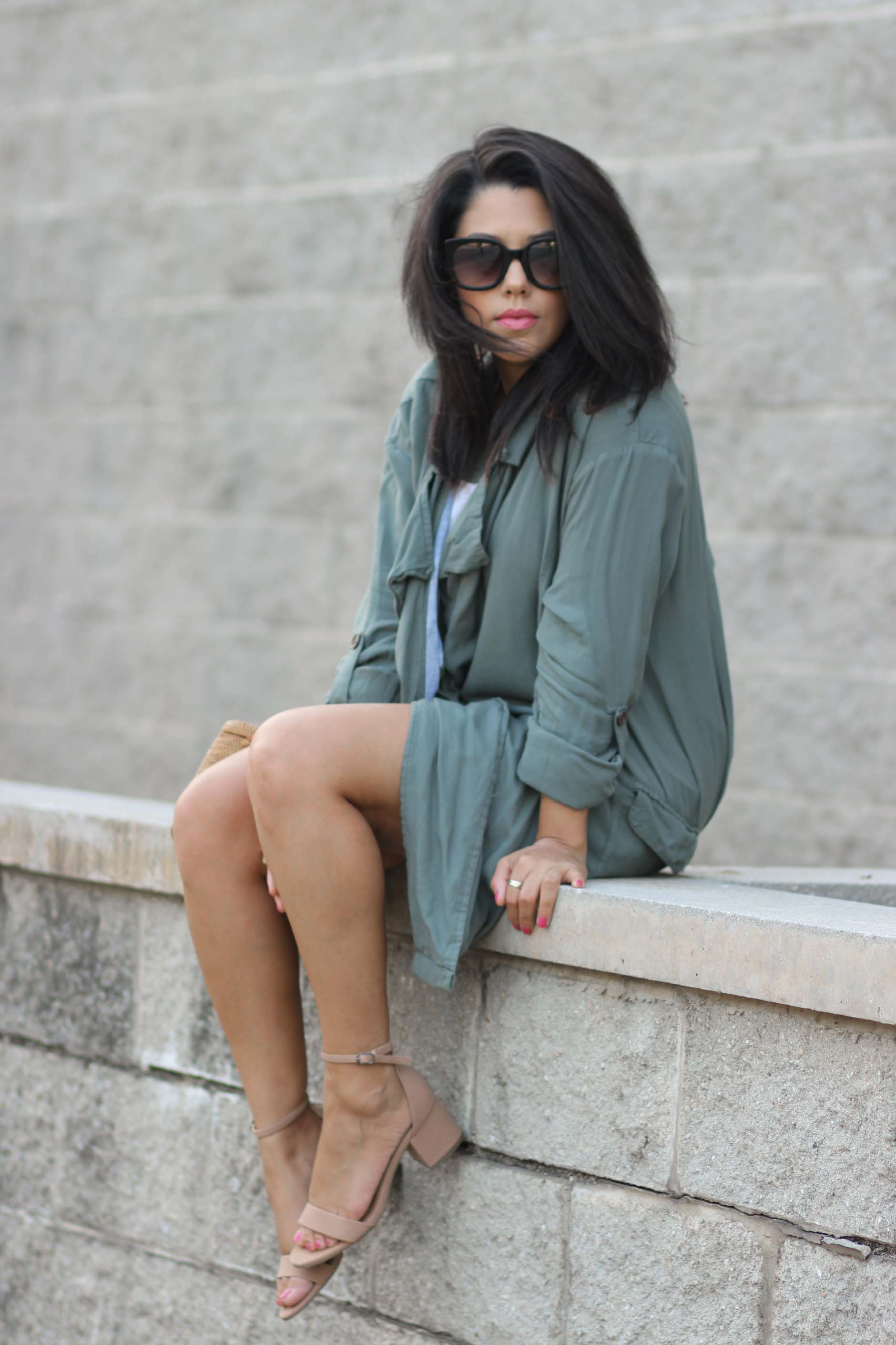 lifestyle blogger naty michele sitting down wearing a trench coat
