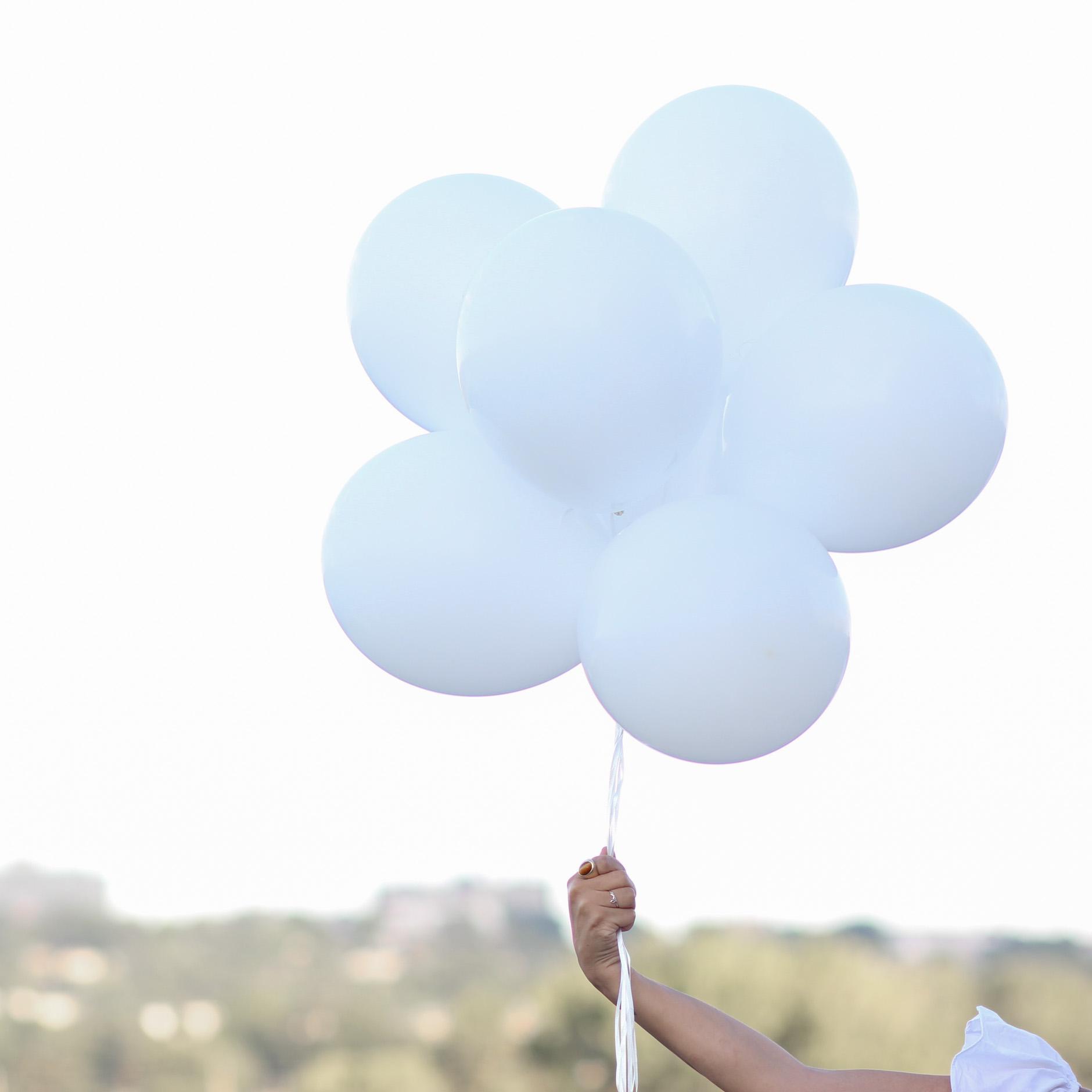 lifestyle blogger naty michele holding white balloons