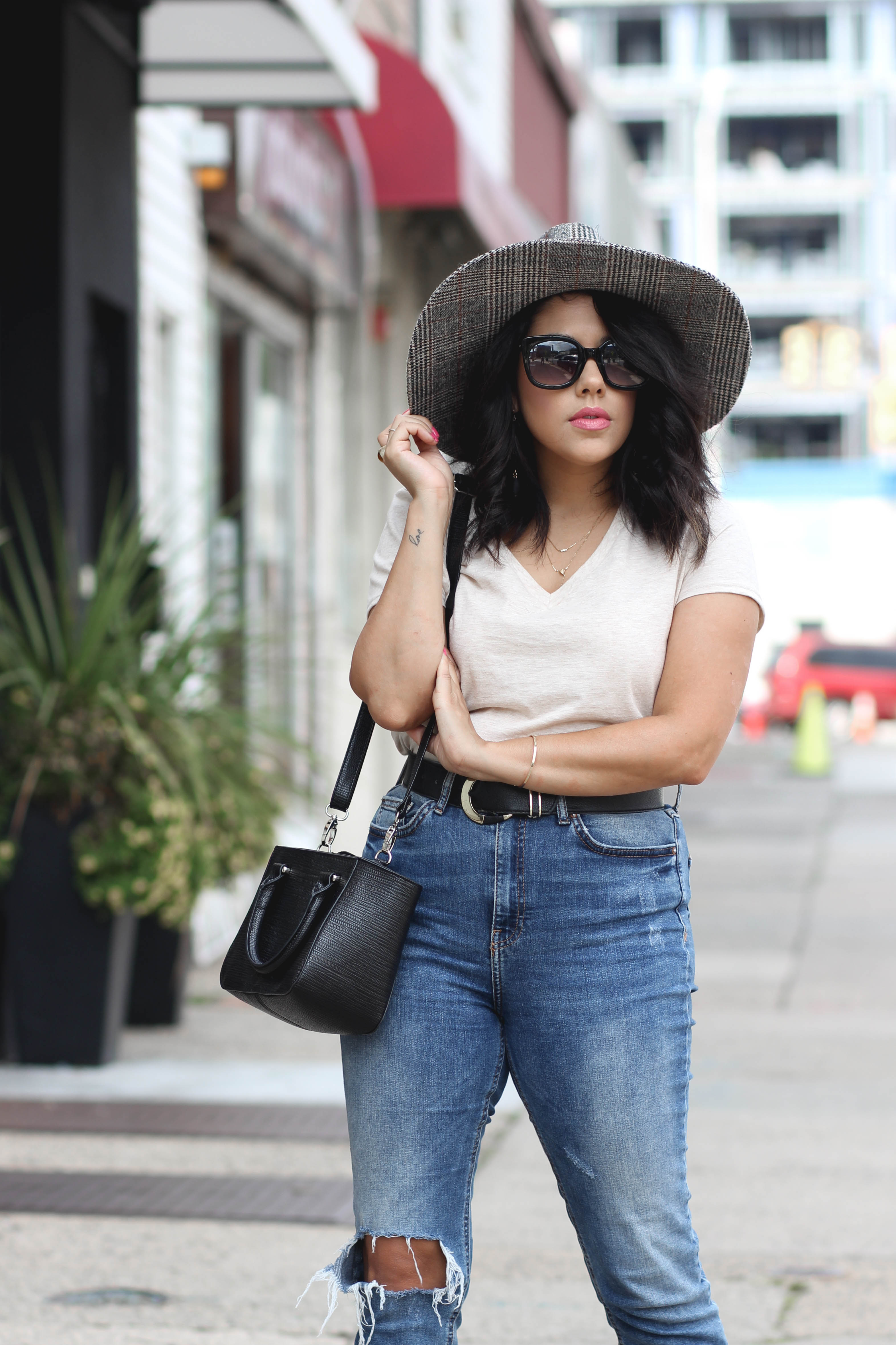 lifestyle blogger naty michele wearing a wide brim hat with denim and a tshirt