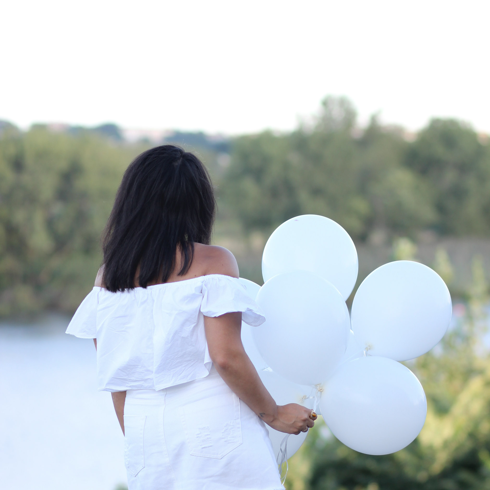 back of lifestyle blogger naty michele holding white balloons