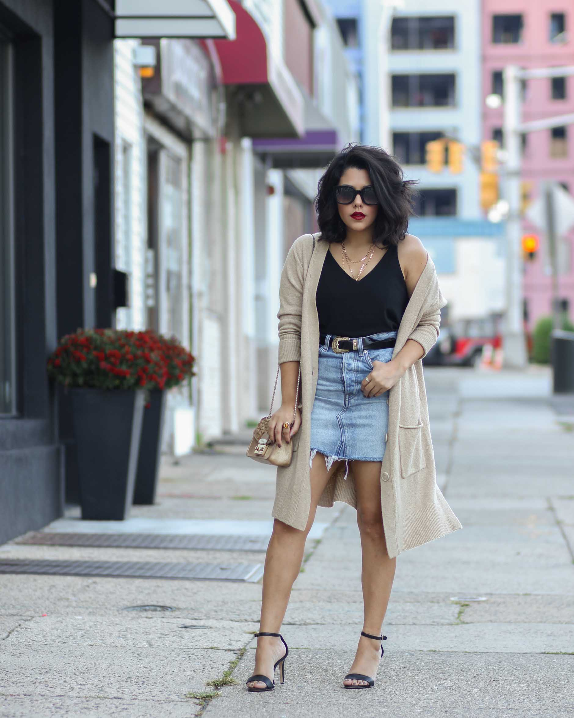 style blogger naty michele wearing a denim skirt and oversized cardigan