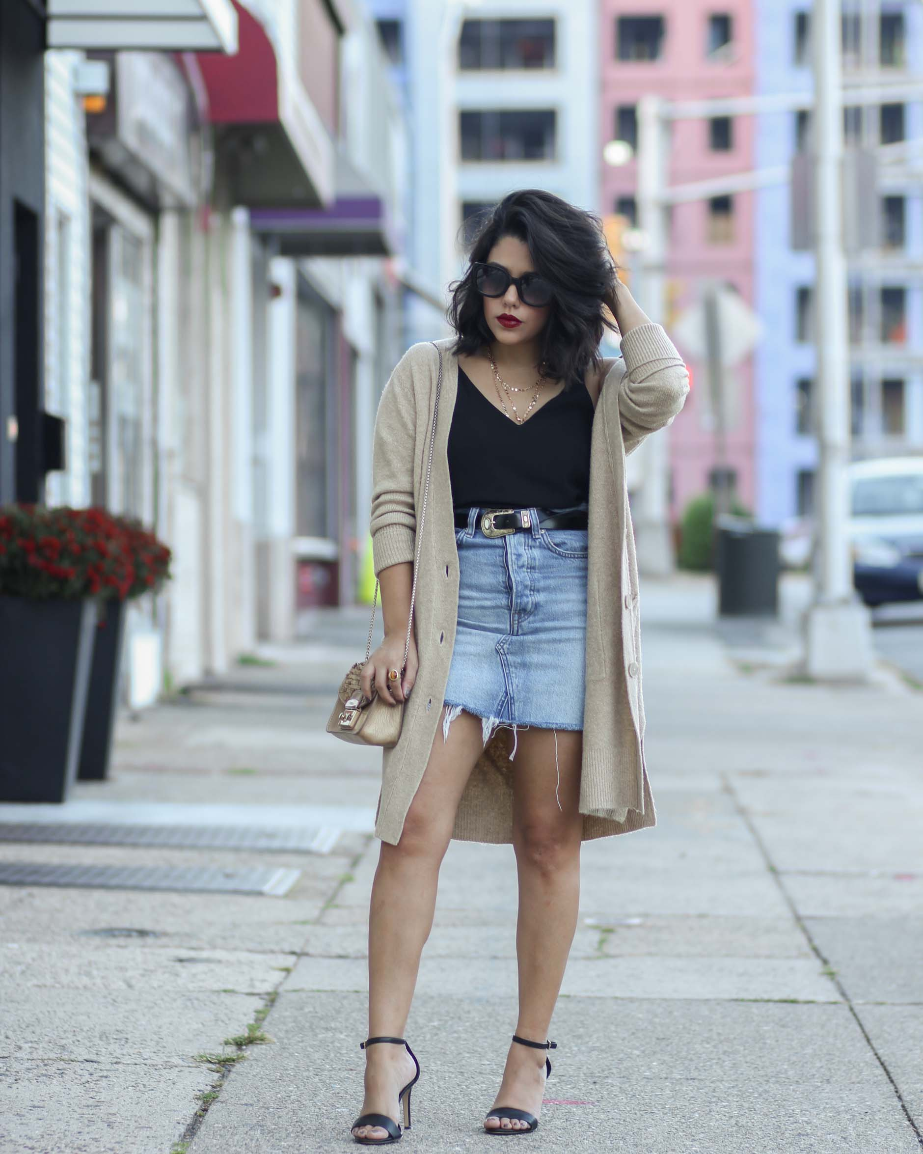 street style shot of style blogger naty michele wearing an oversized cardigan with a denim skirt and belt
