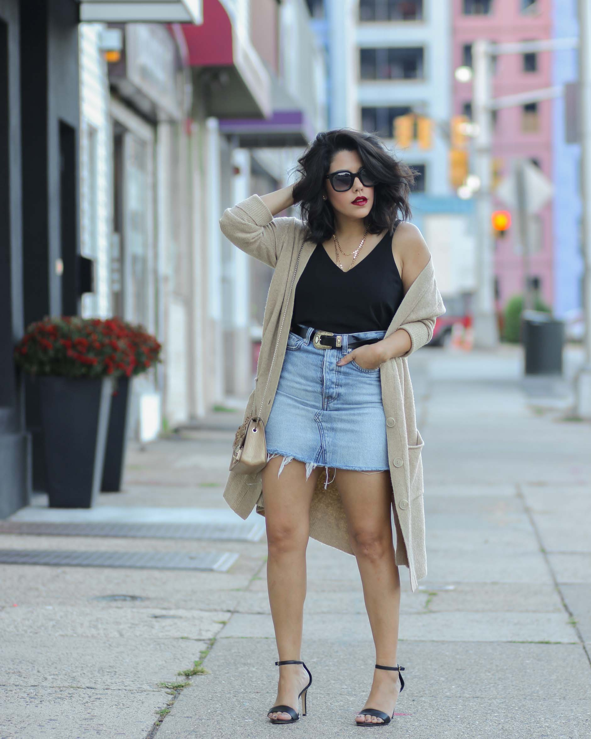 style blogger naty michele wearing denim skirt with a belt and oversized cardigan