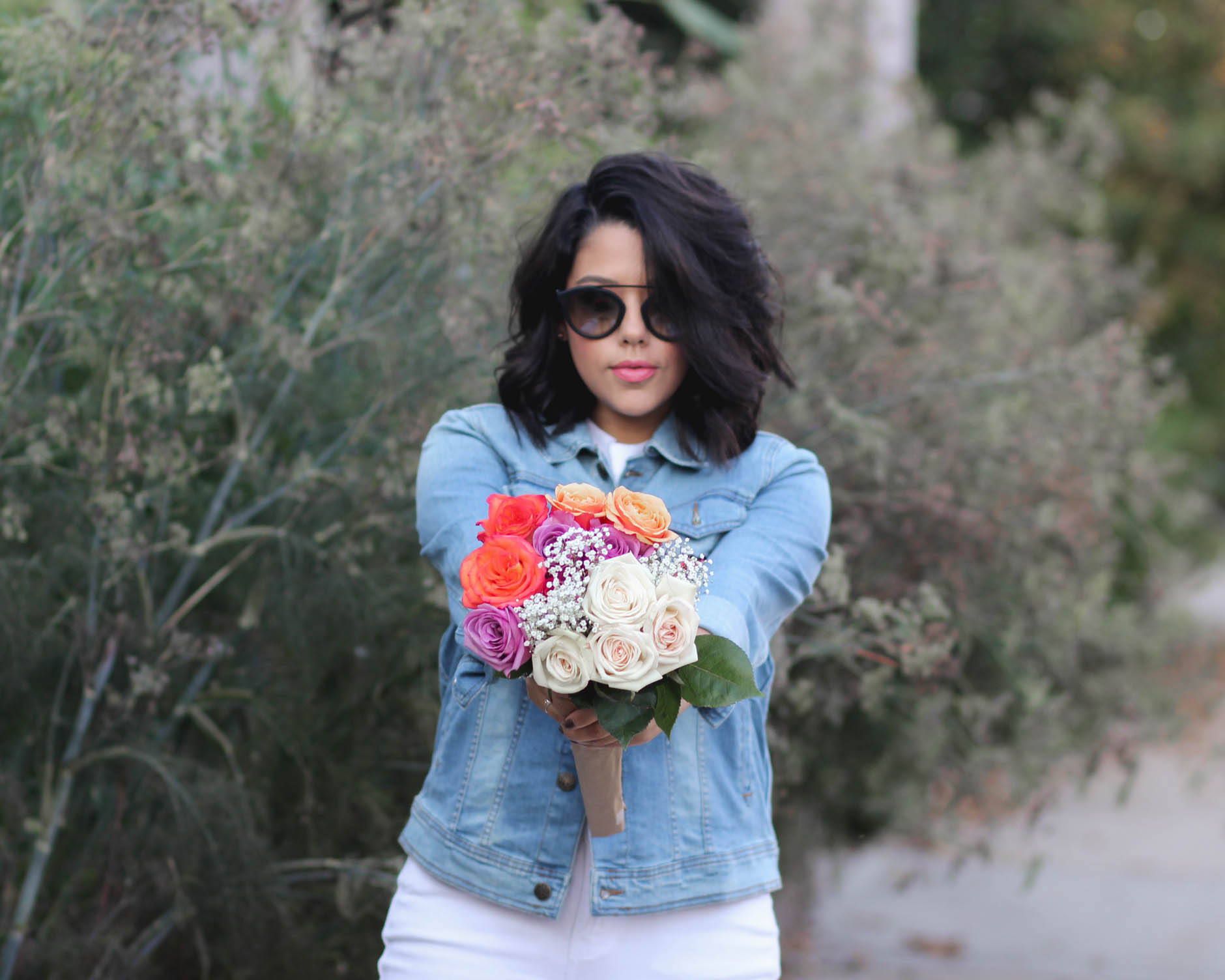 lifestyle blogger naty michele holding roses and wearing a denim jacket
