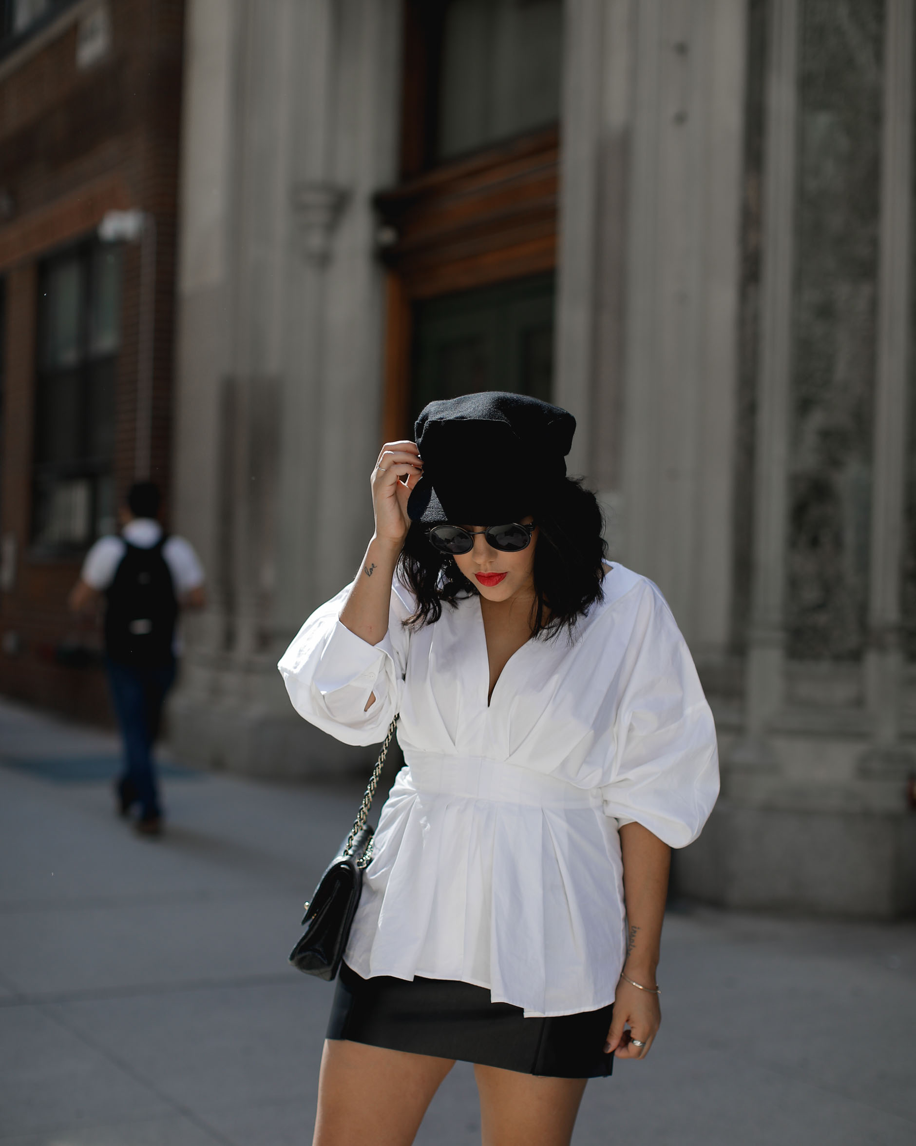 lifestyle blogger naty michele wearing statement sleeves and cabbie hat at nyfw