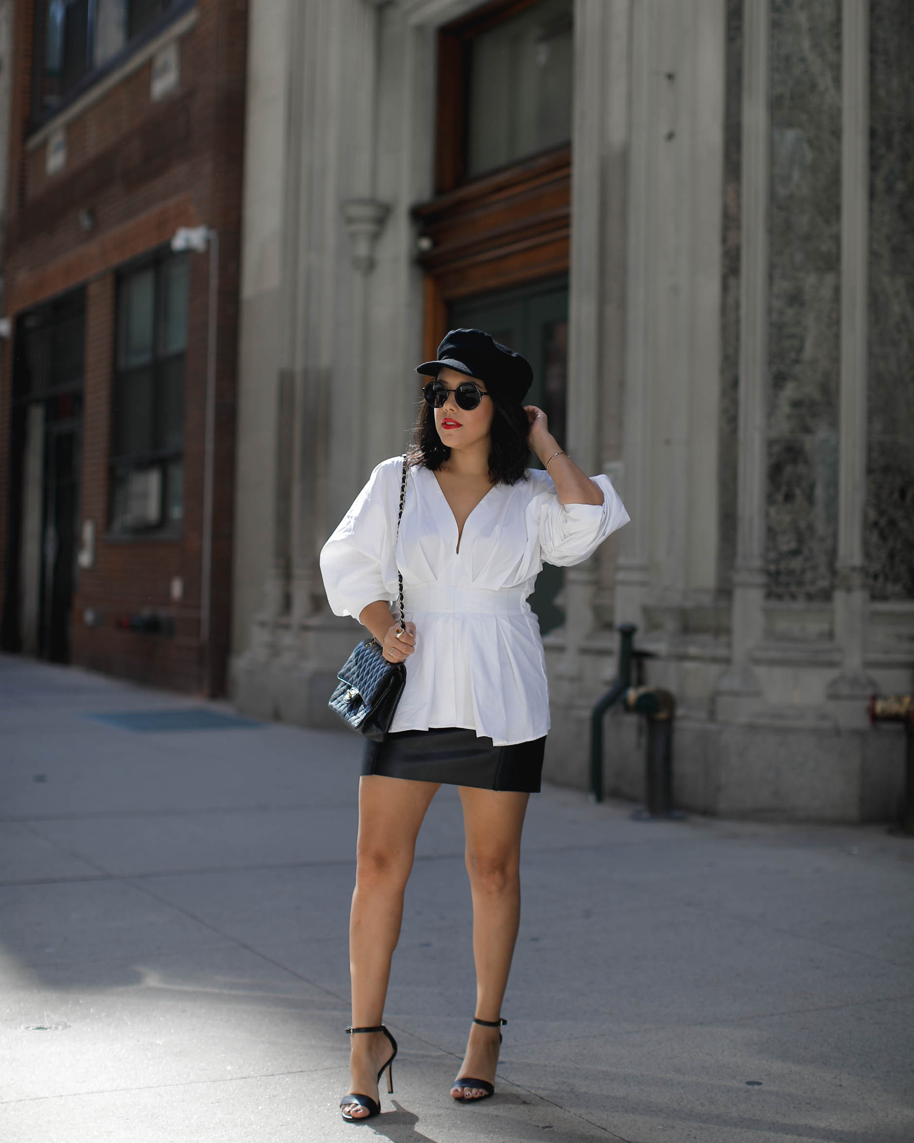 lifestyle blogger naty michele wearing statement sleeves and a cabbie hat at nyfw