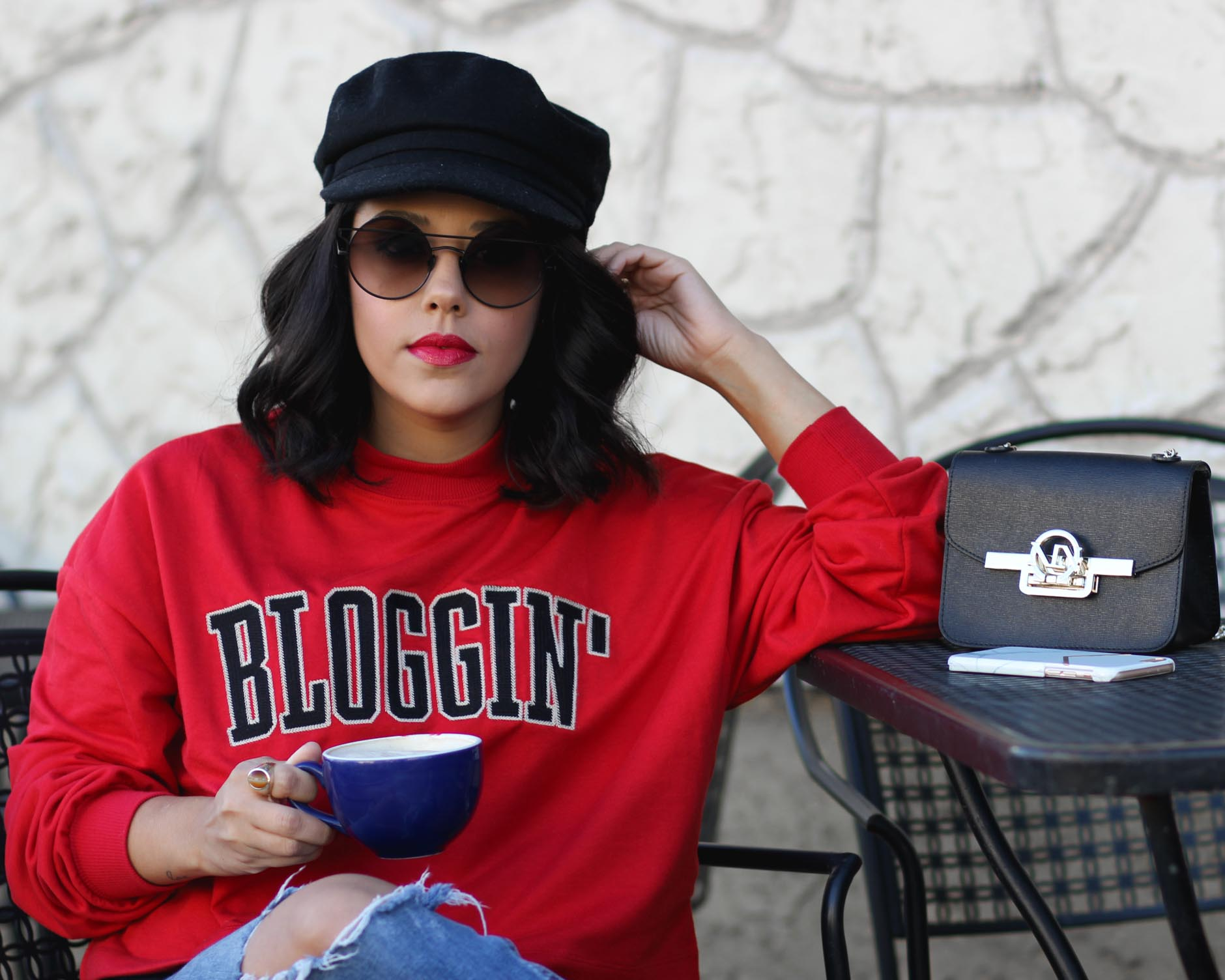 lifestyle blogger naty michele wearing a blogging sweatshirt and drinking coffee