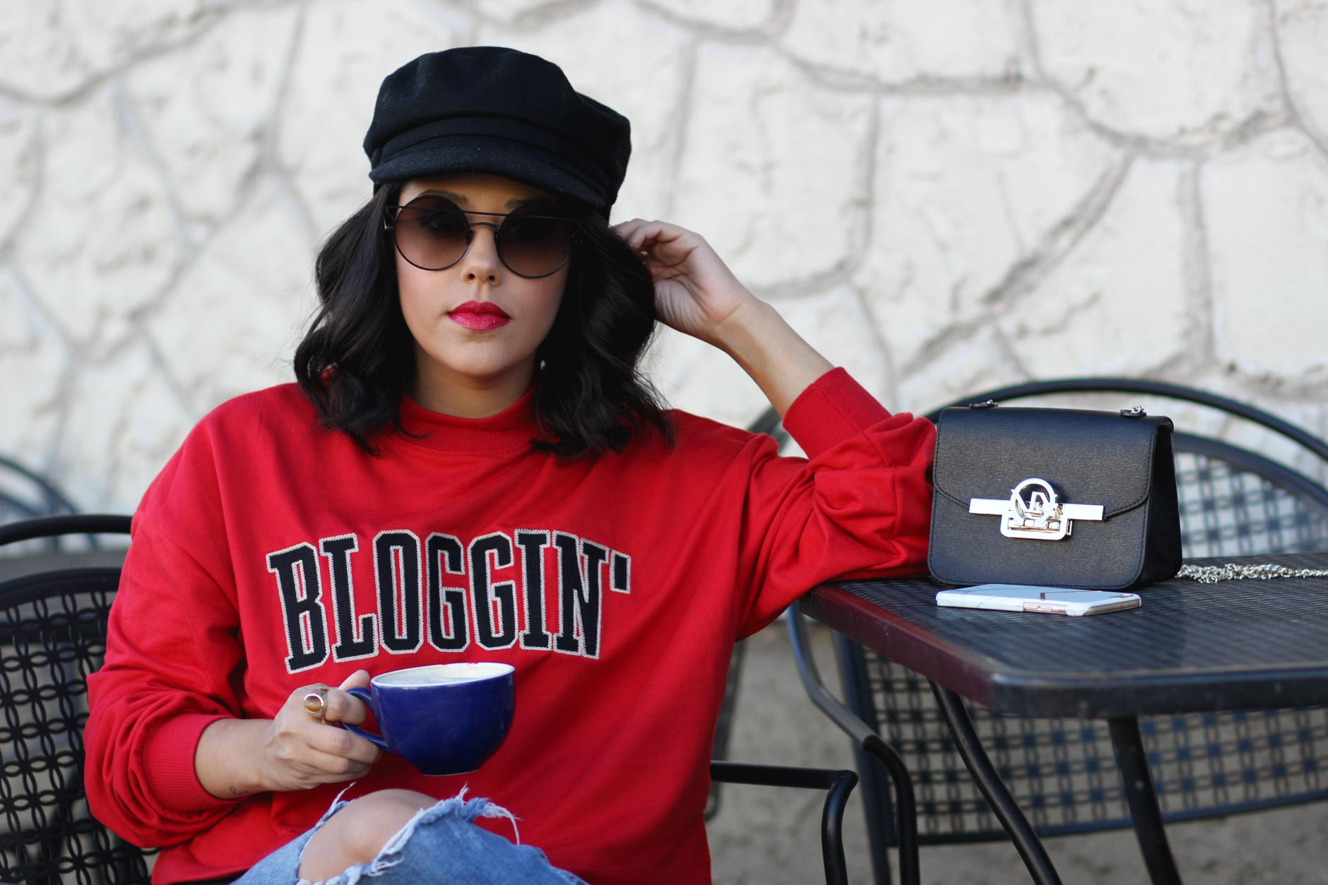 lifestyle blogger naty michele wearing a blogging sweatshirt holding coffee