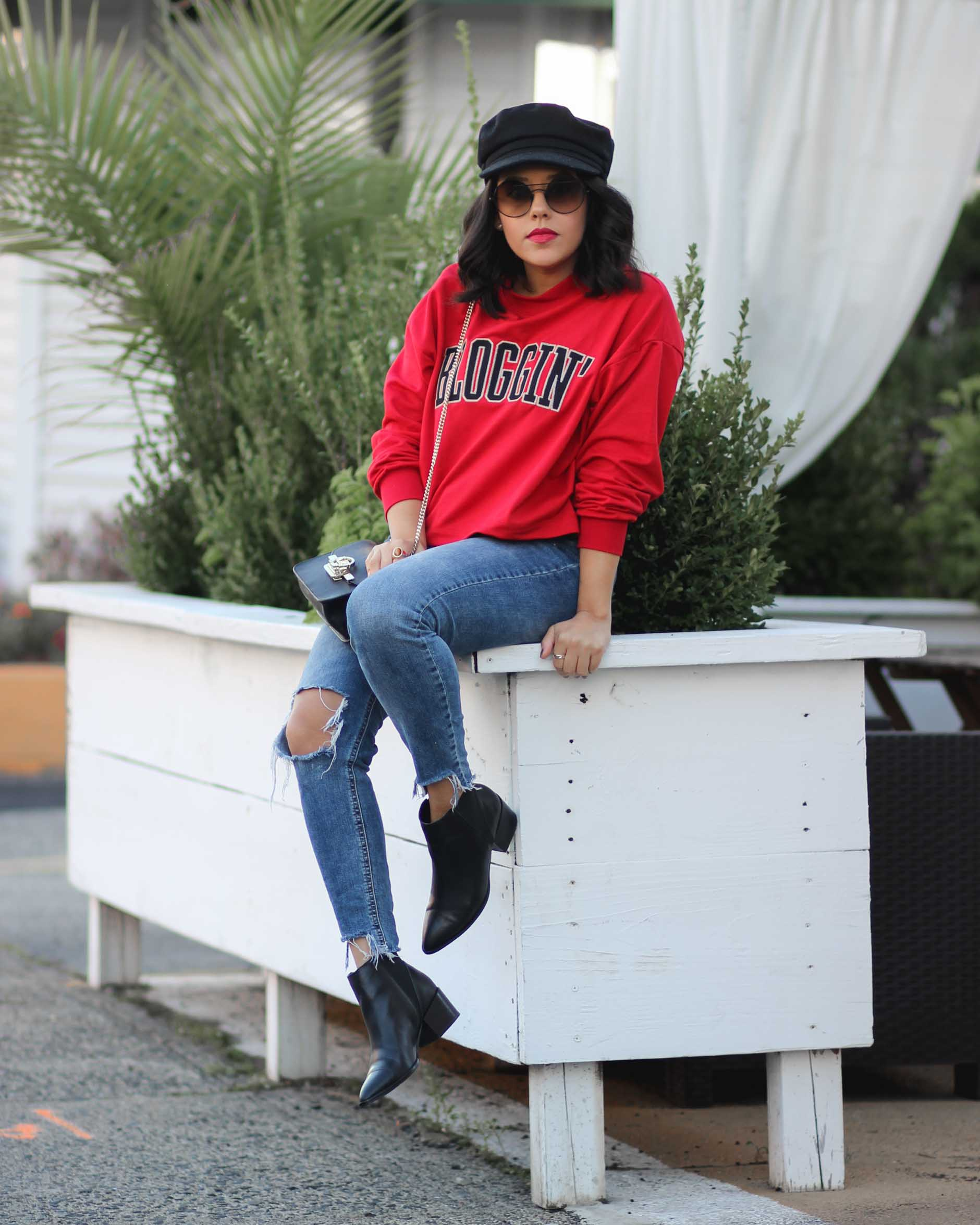 lifestyle blogger naty michele wearing a blogging sweatshirt and jeans with booties