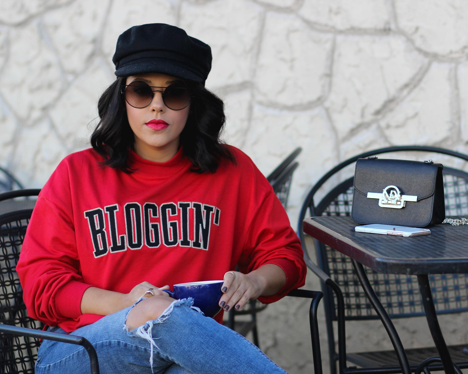 lifestyle blogger naty michele wearing a blogging sweatshirt and holding coffee