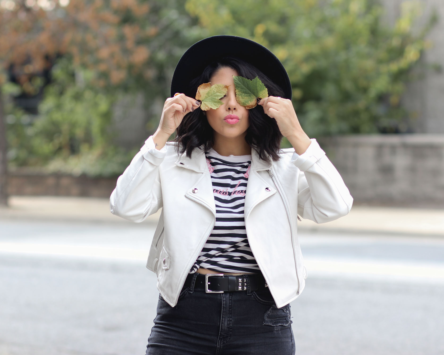 lifestyle blogger naty michele wearing a white faux leather jacket and holding leaves
