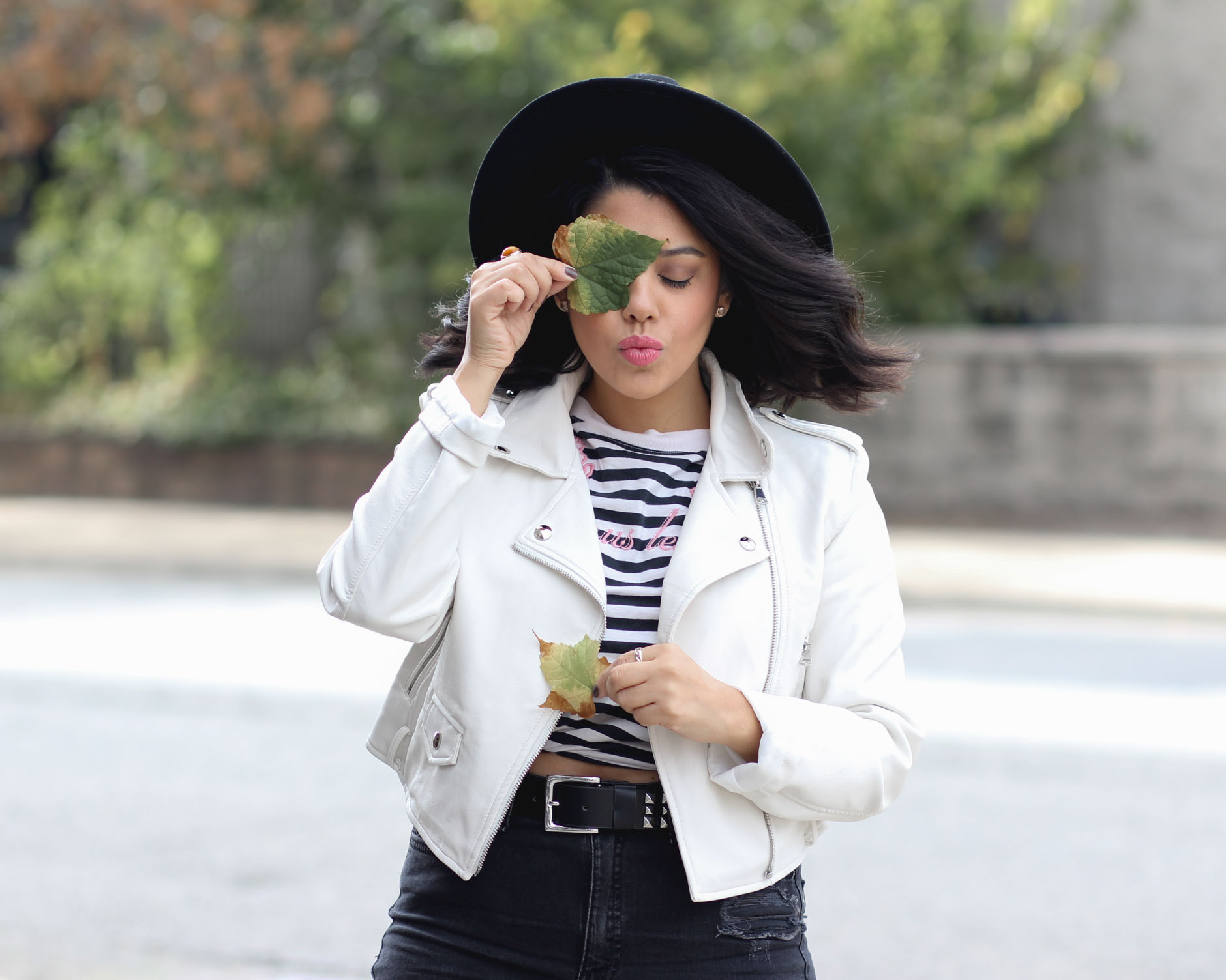 lifestyle blogger naty michele wearing a faux leather jacket and holding up a leaf