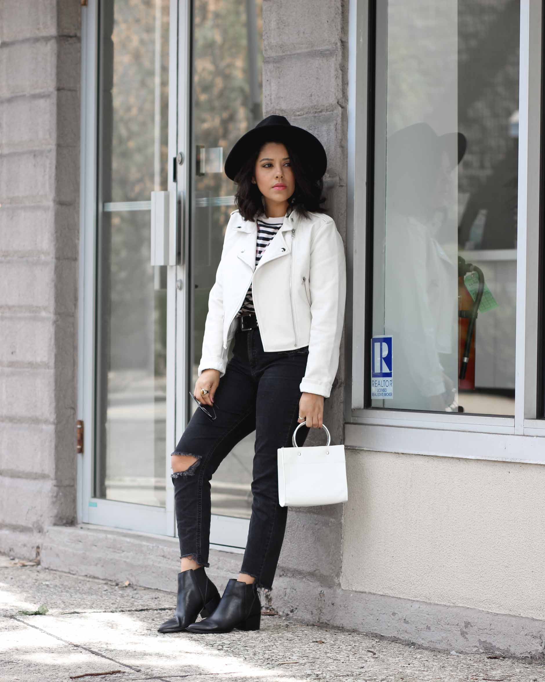 lifestyle blogger naty michele wearing a white faux leather jacket and black denim with black boots