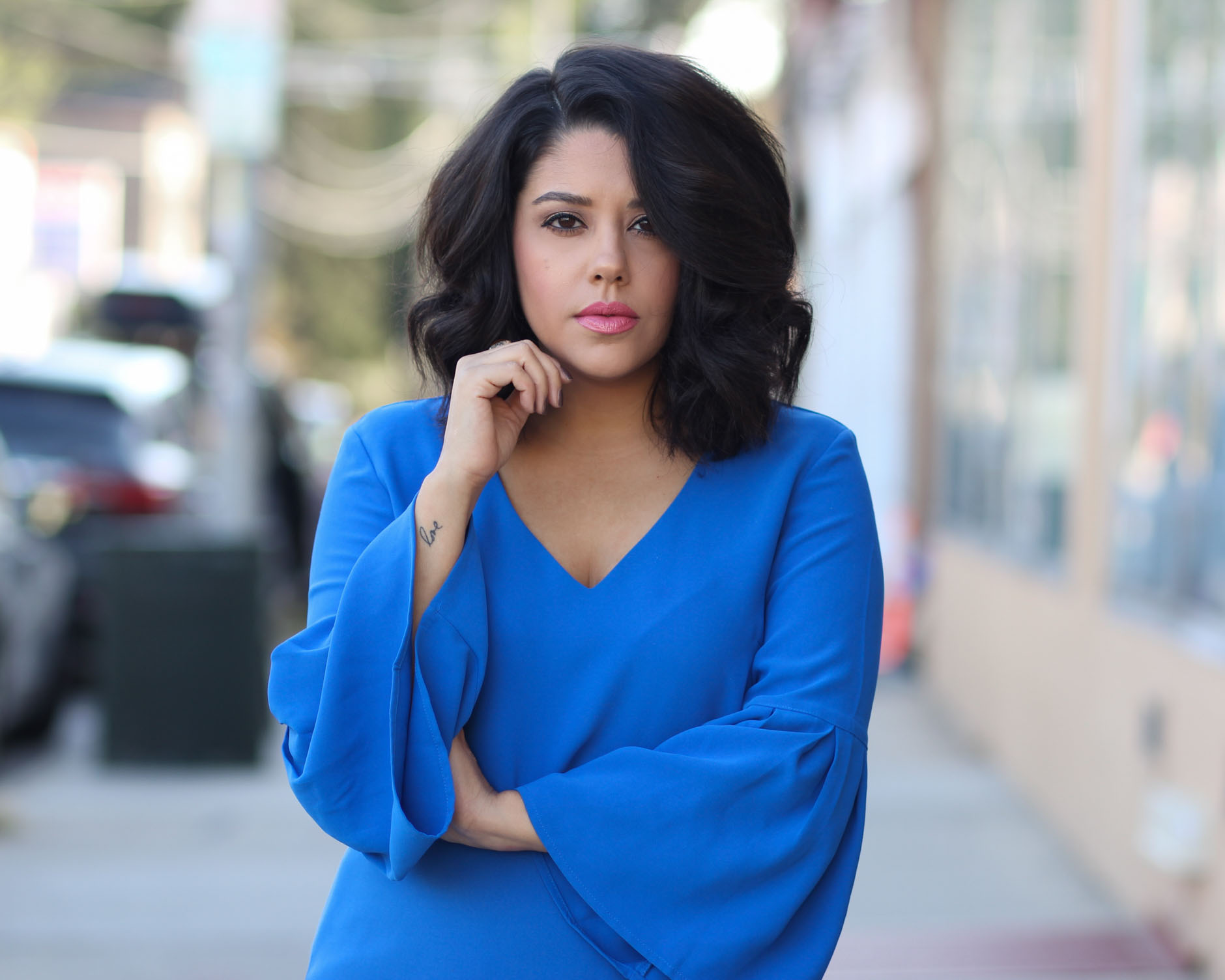 lifestyle blogger naty michele with short curly hair wearing blue