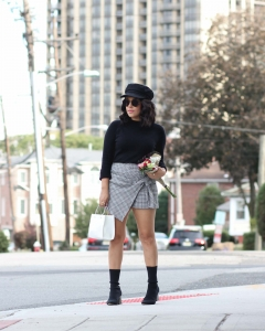 lifestyle blogger naty michele holding flowers wearing a plaid skort and sock boots