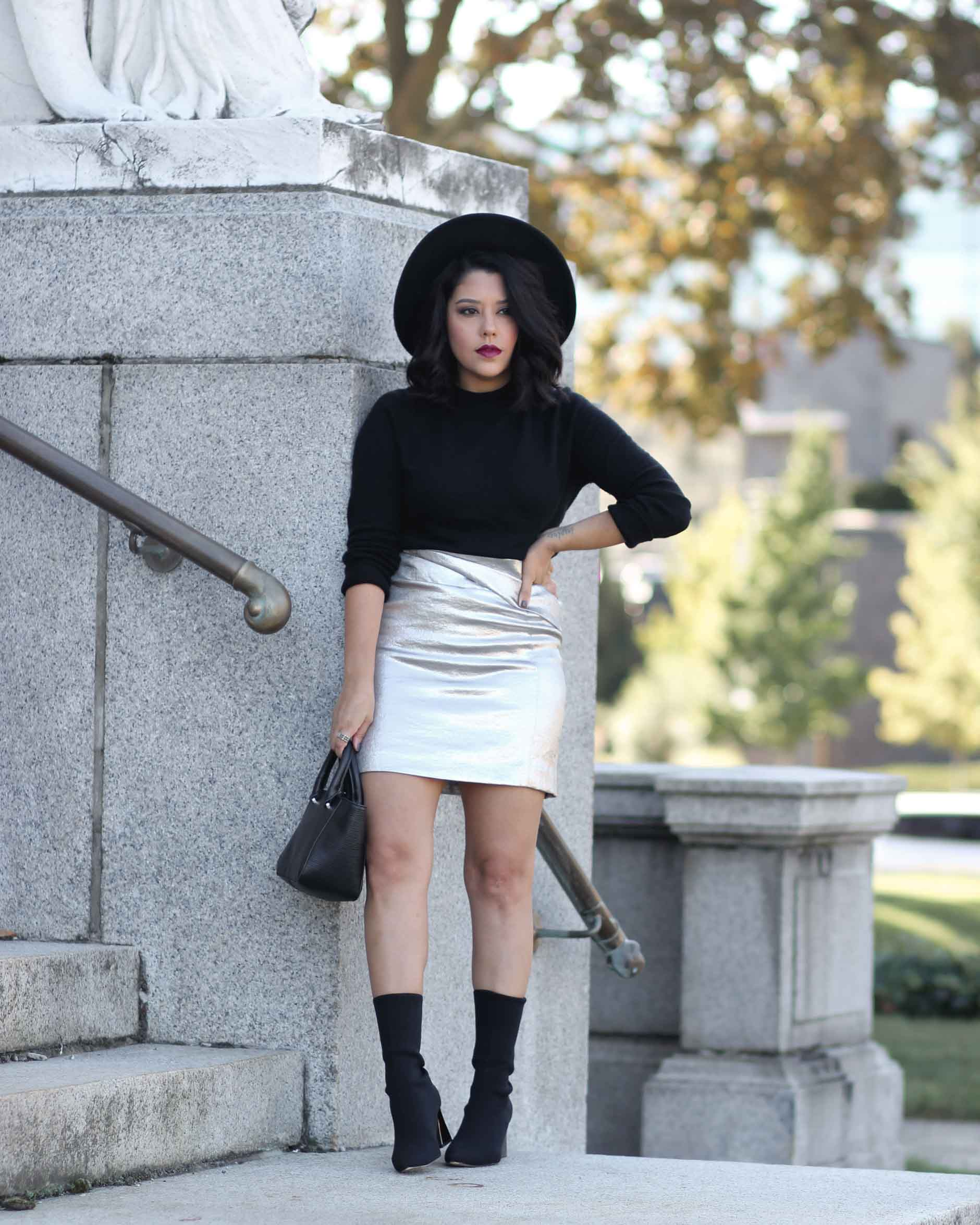 lifestyle blogger naty michele wearing a silver skirt with black sock boots