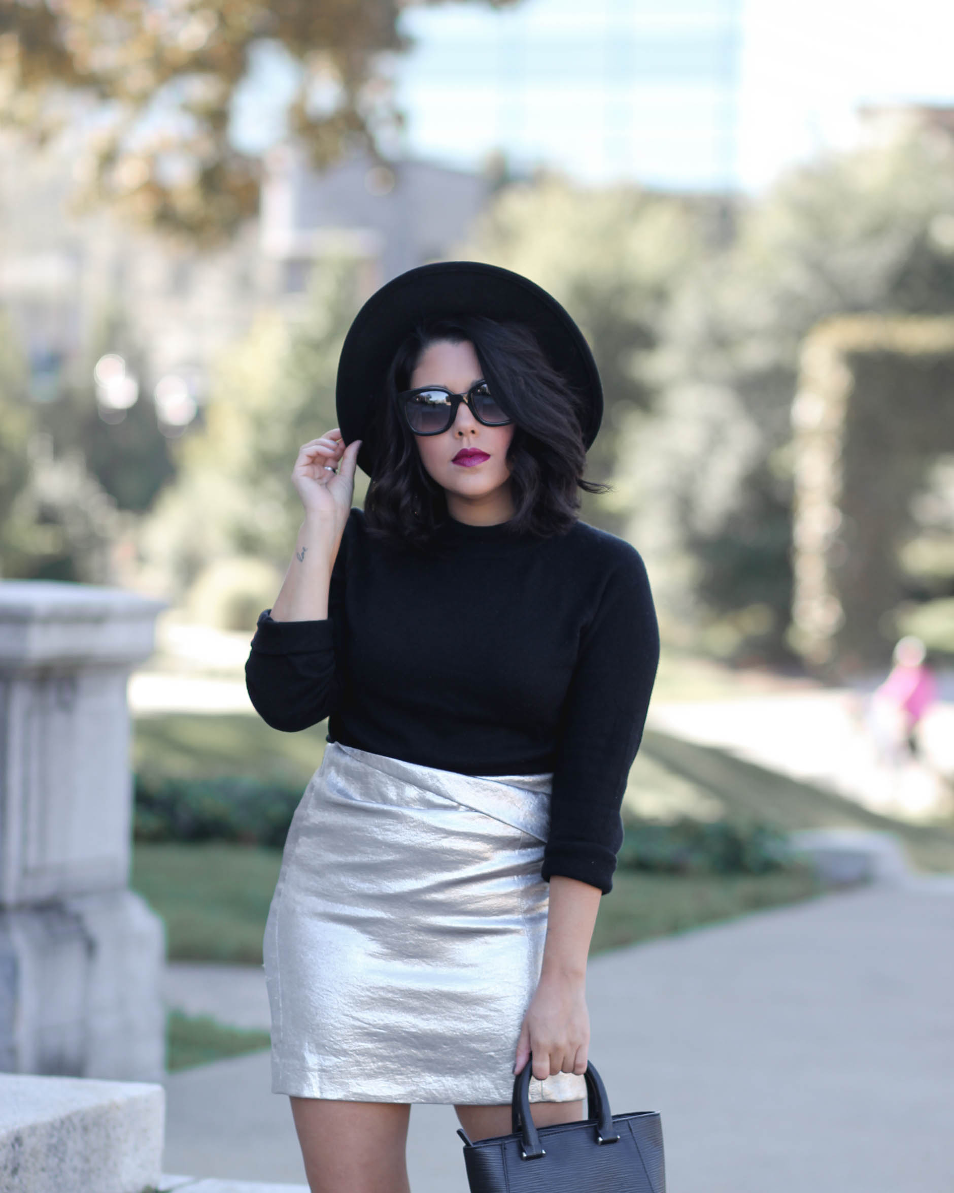 lifestyle blogger naty michele wearing a black sweater and silver skirt and wide brim hat