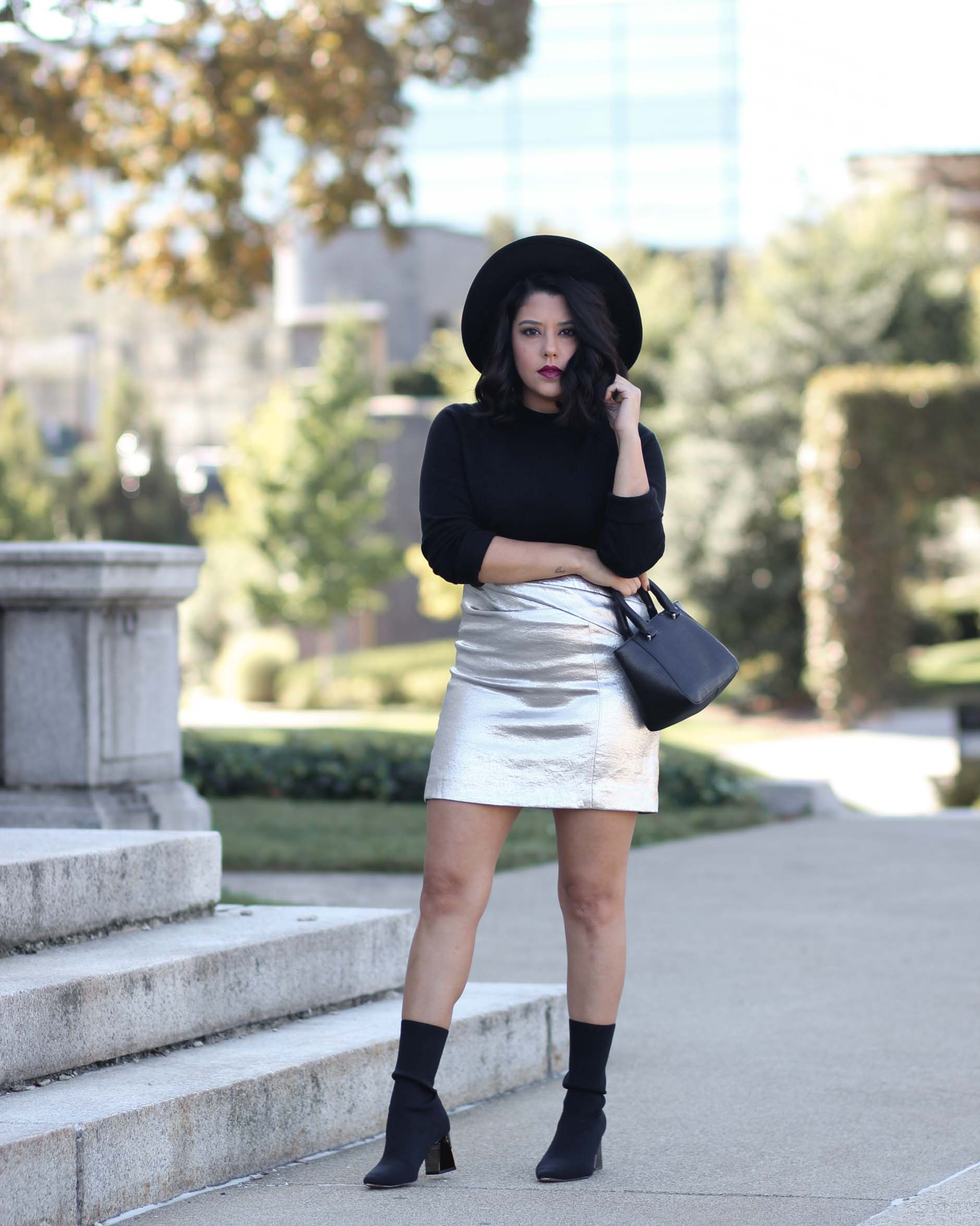 lifestyle blogger naty michele wearing a silver skirt and black sock boots