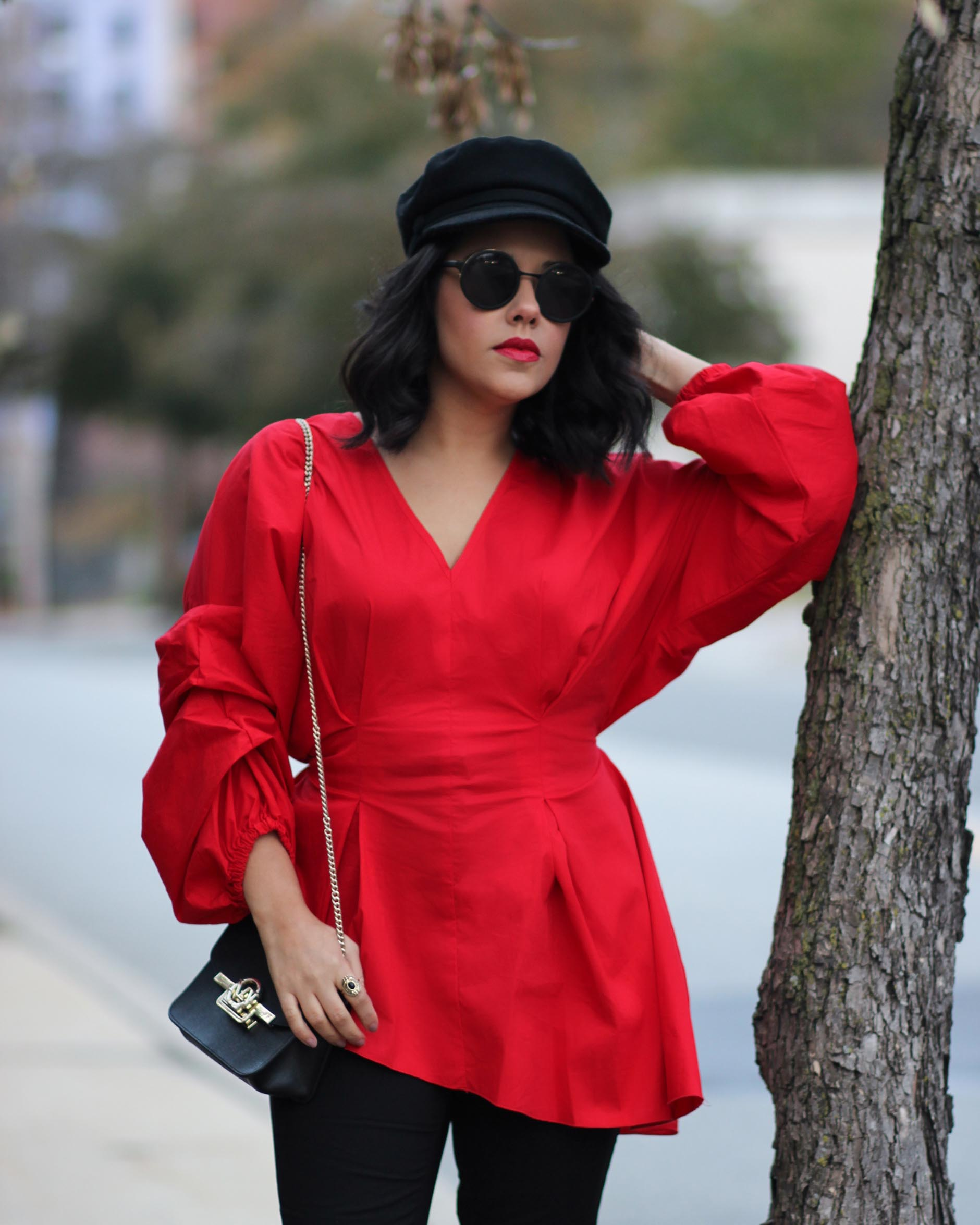 naty michele wearing a red puffy sleeve top from project runway