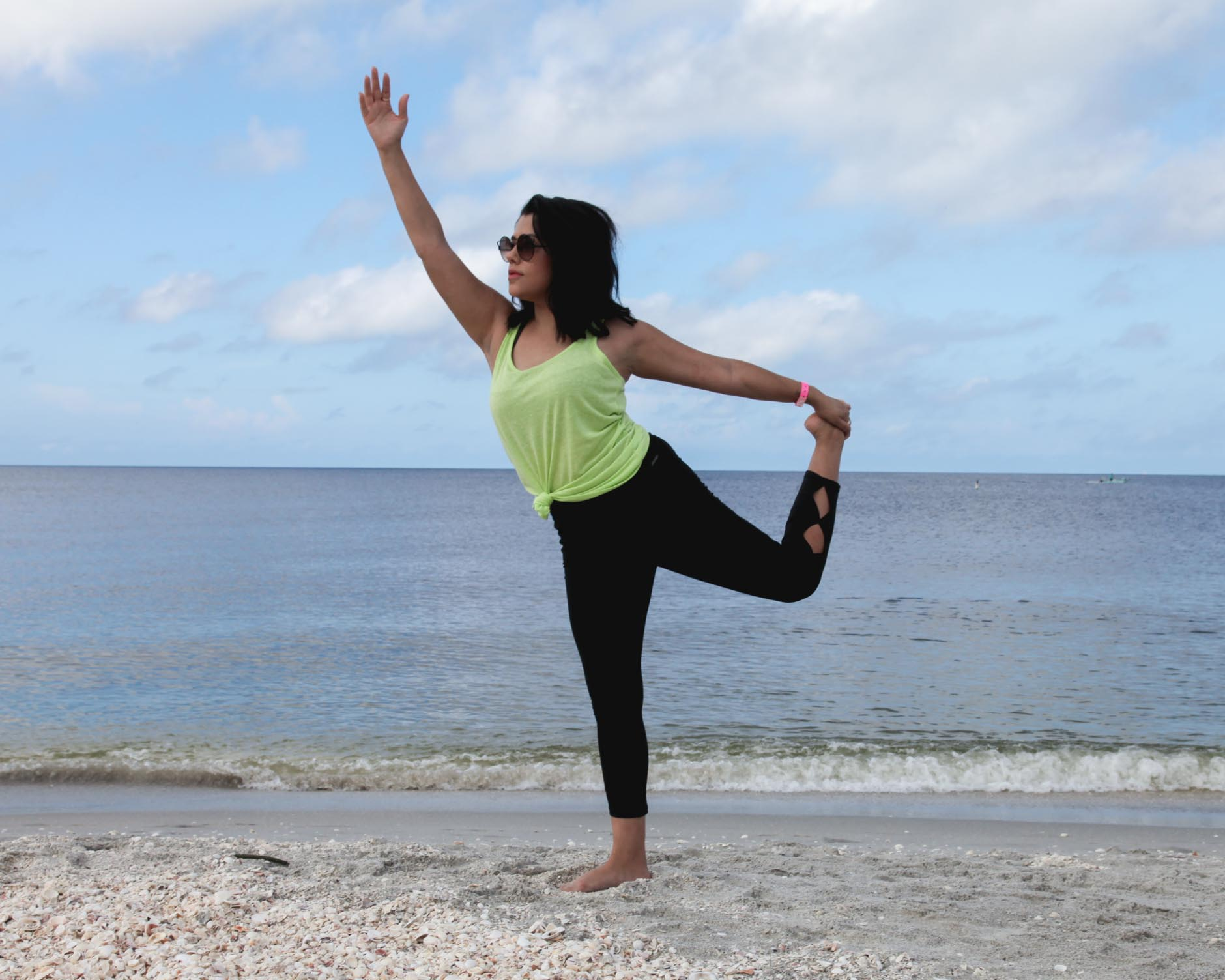lifestyle blogger naty michele wearing jockey doing beach yoga
