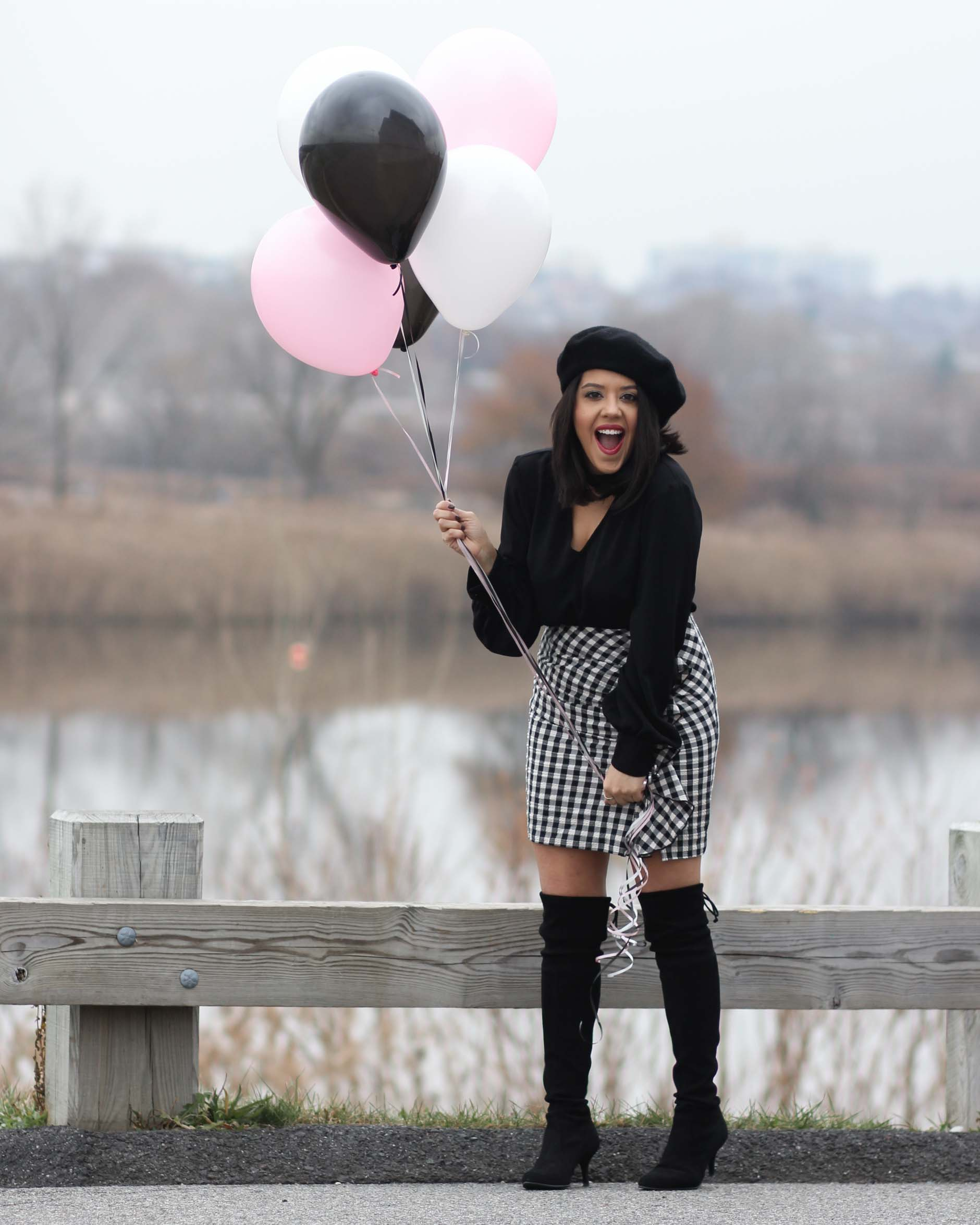 lifestyle blogger naty michele wearing otk boots with a beret and gingham skirt holding balloons