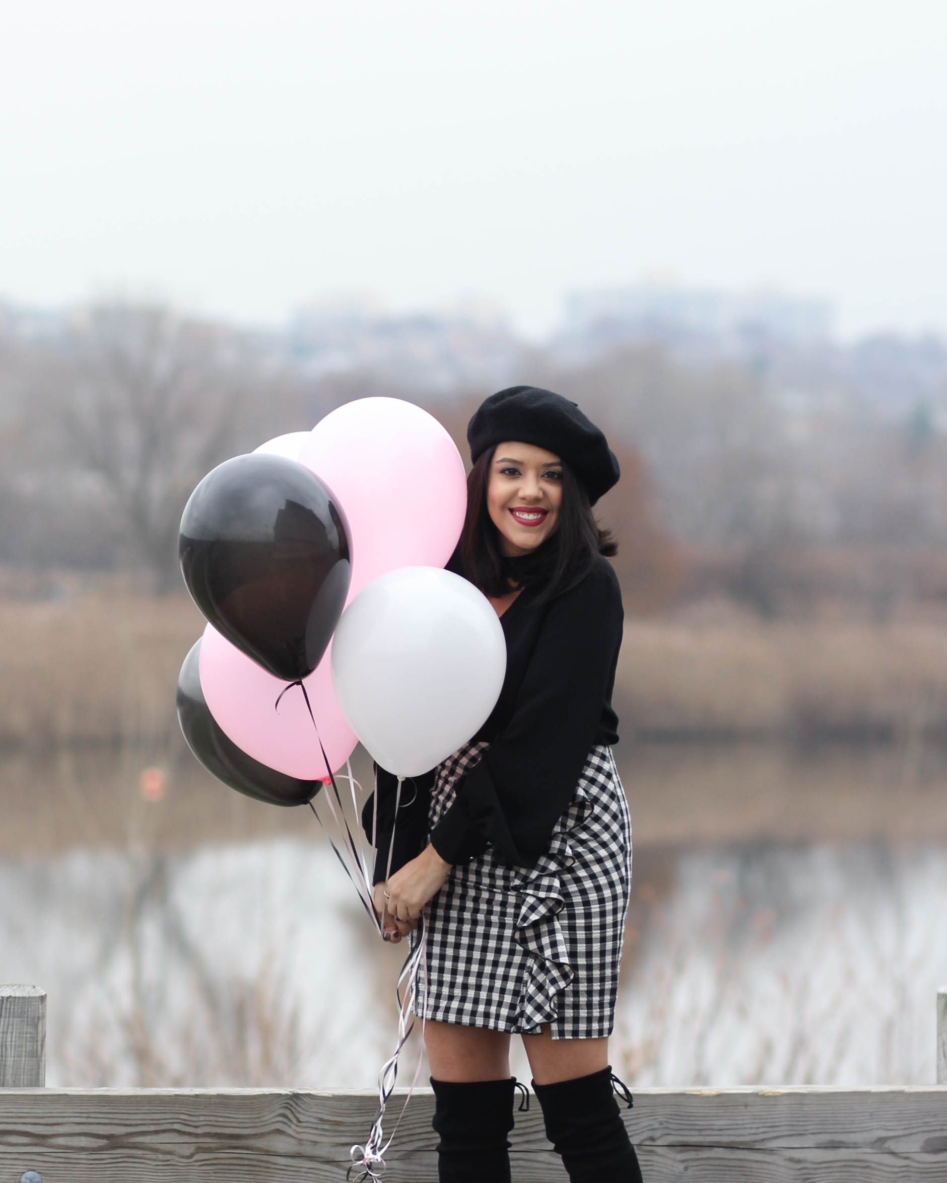 lifestyle blogger naty michele wearing beret and holding balloons