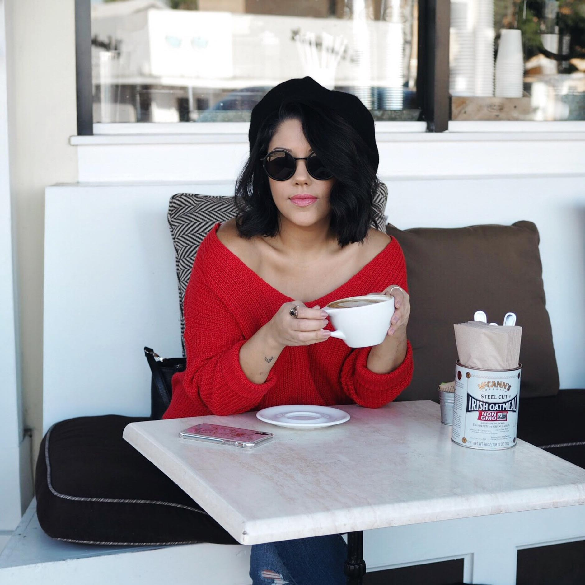 naty michele wearing off the shoulder sweater drinking coffee