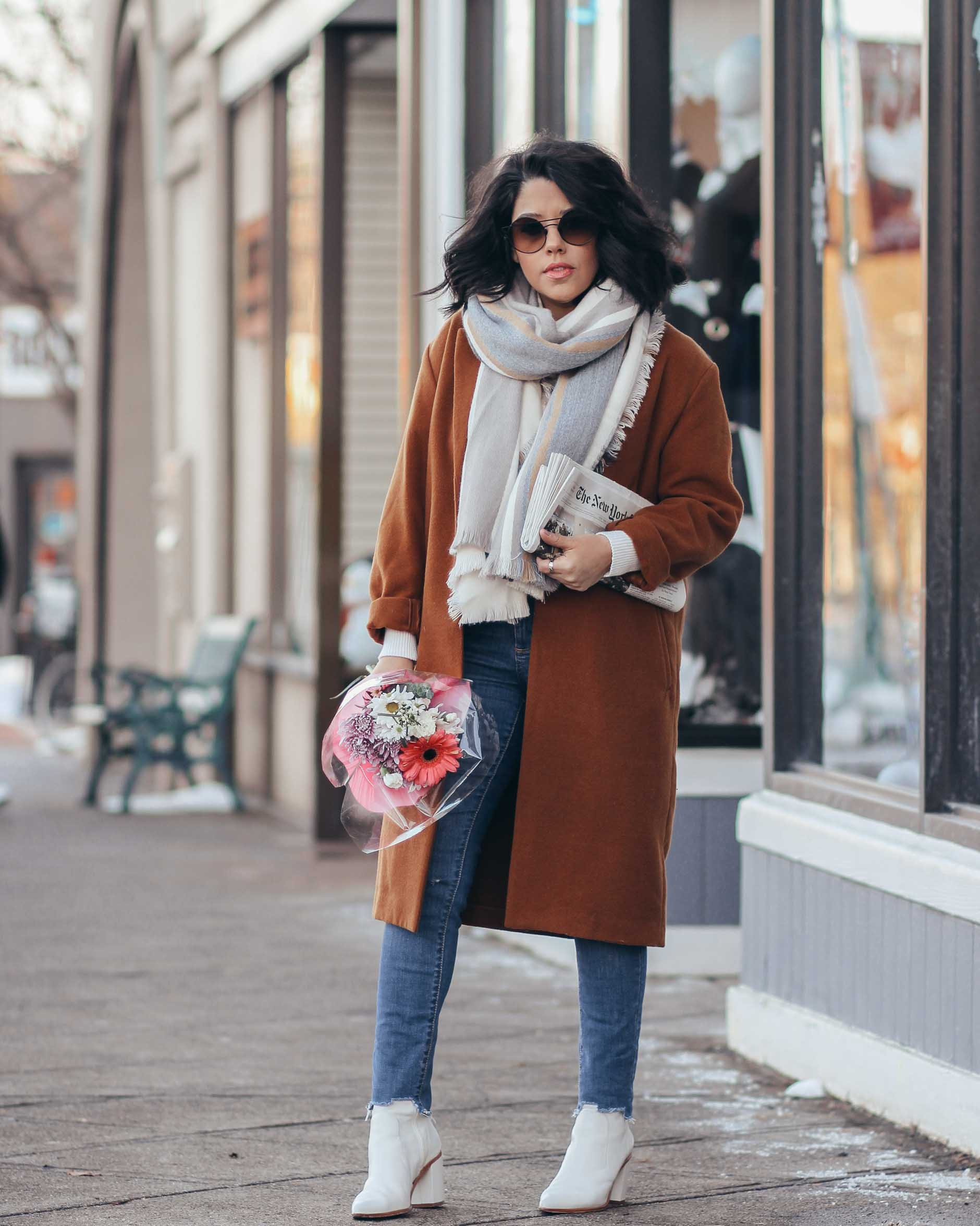 lifestyle blogger naty michele wearing camel coat with flowers and newspaper