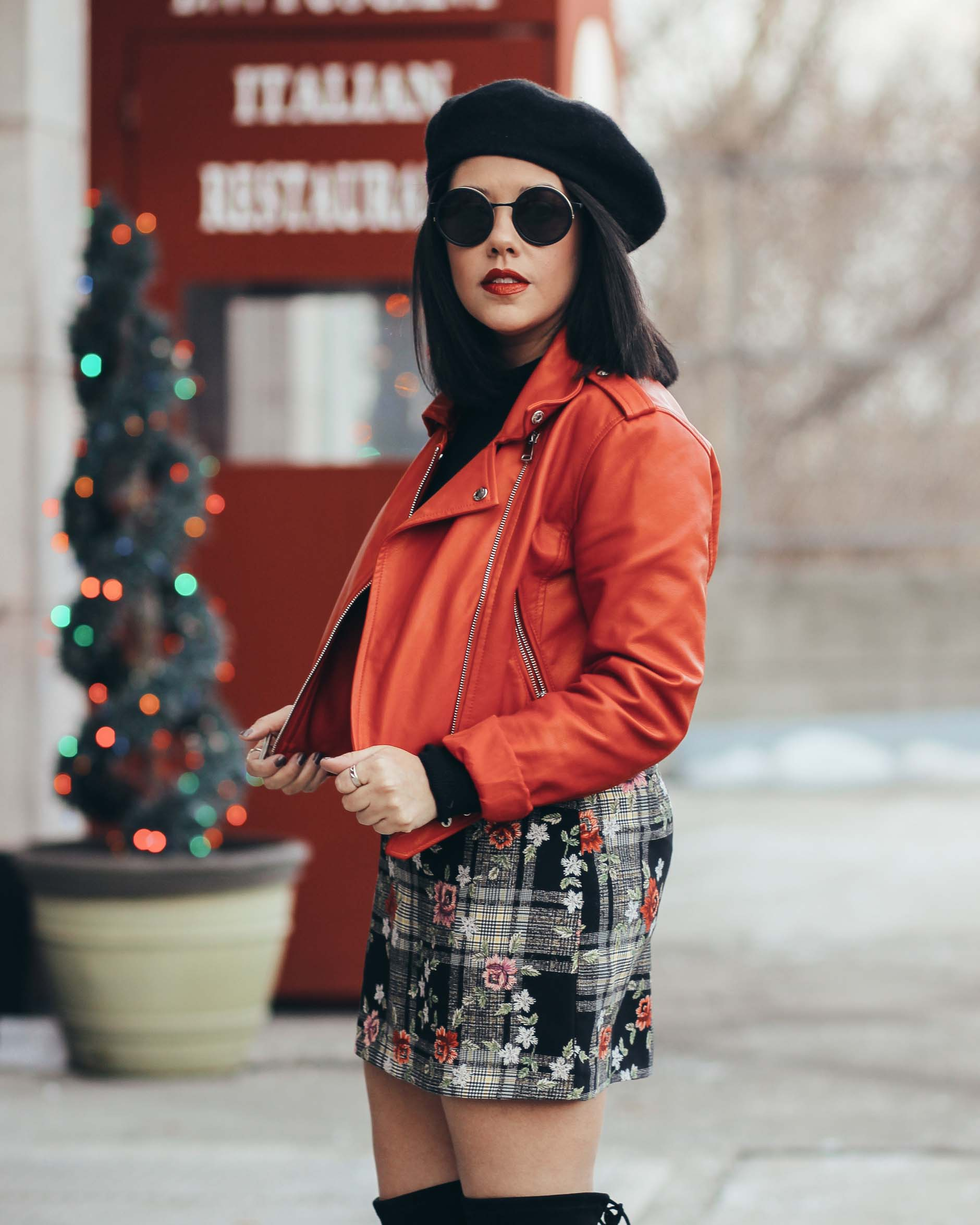naty michele wearing a red moto jacket with floral skirt