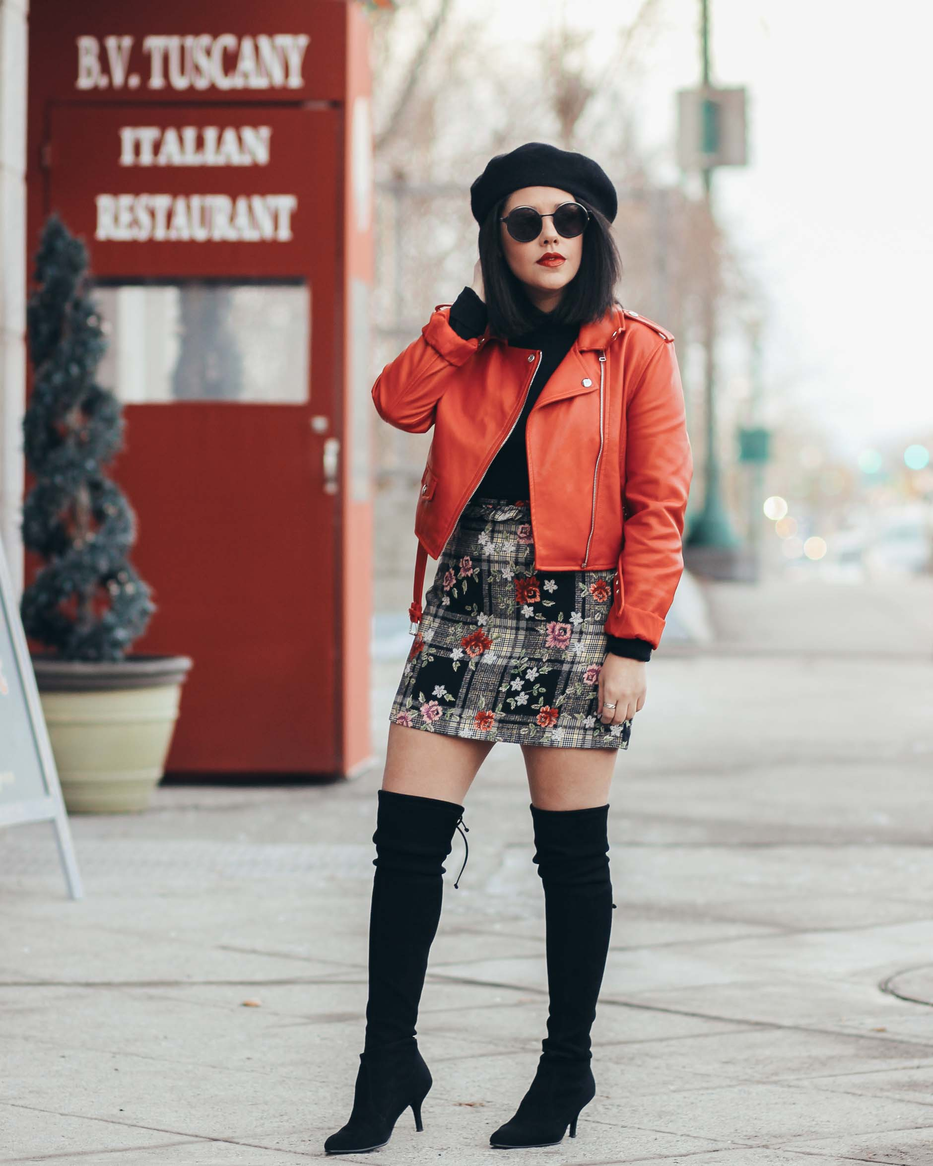 nay michele wearing otk boots with red moto jacket and floral skirt