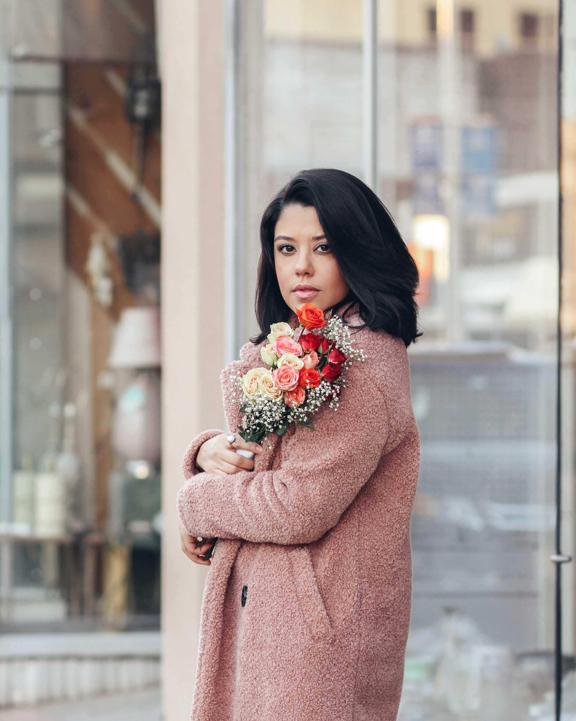 lifestyle blogger naty michele wearing a teddy coat and holding roses