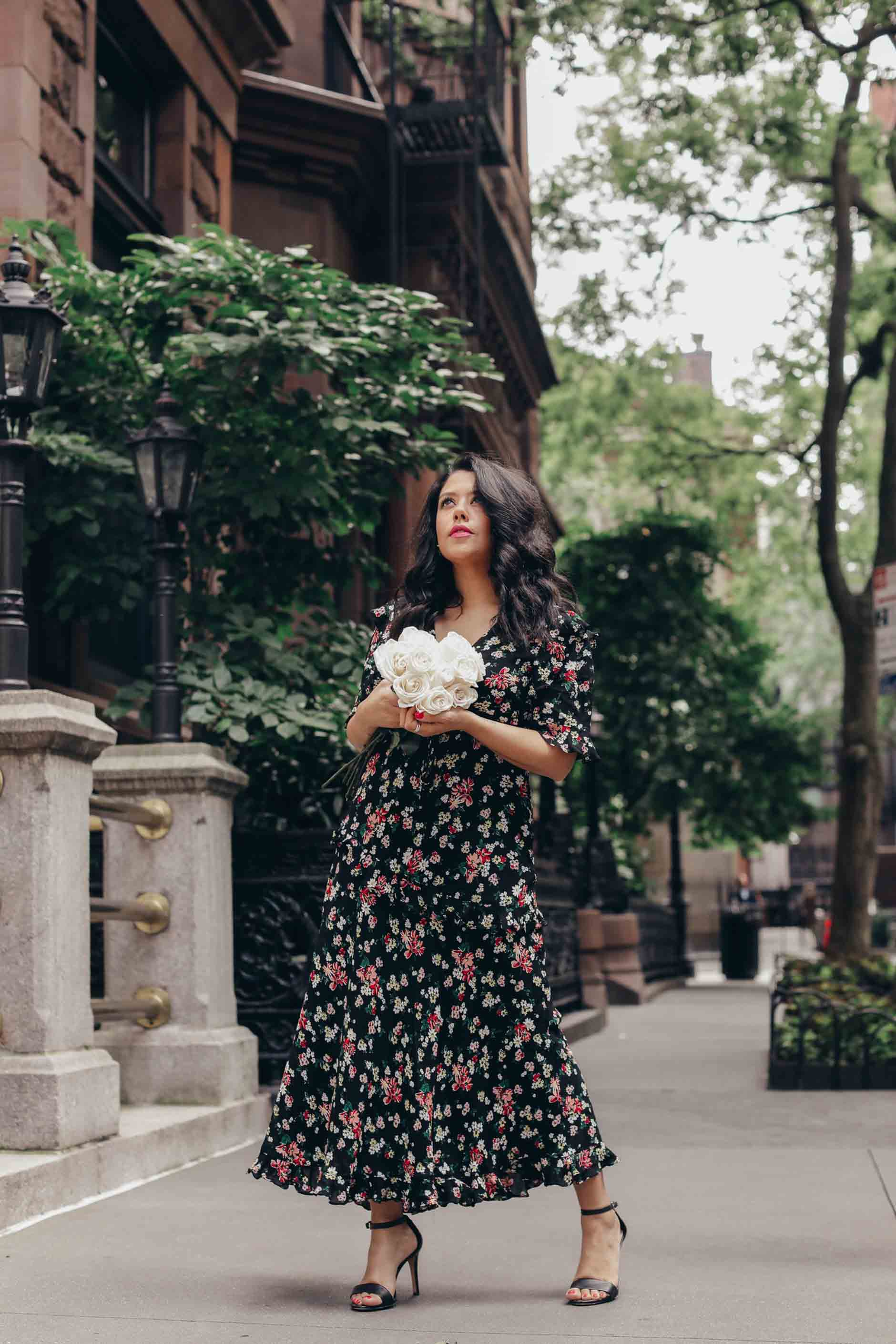 naty michele in a floral dress holding white roses