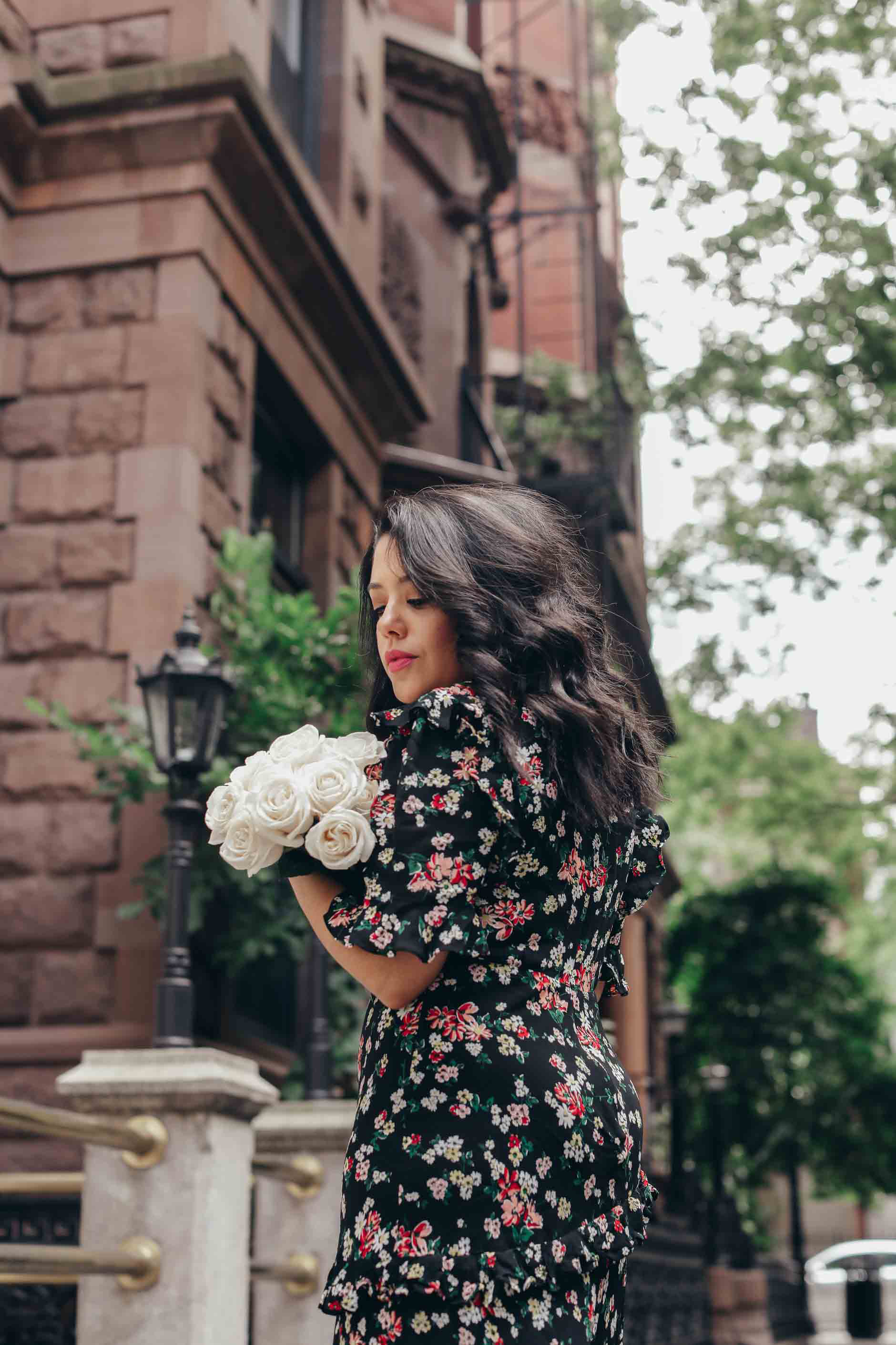 naty michele holding white roses in a floral dress