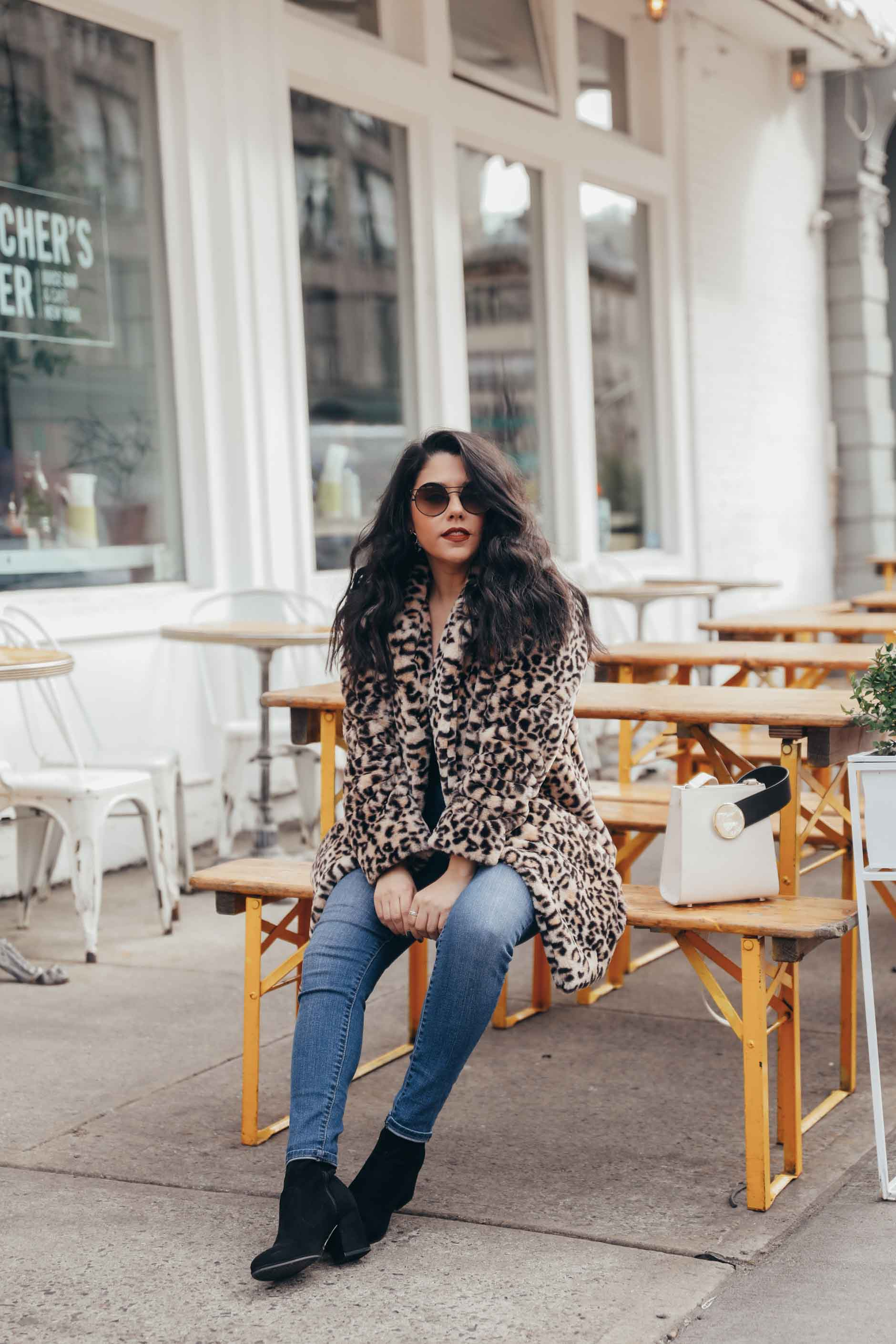naty michele sitting down in leopard coat