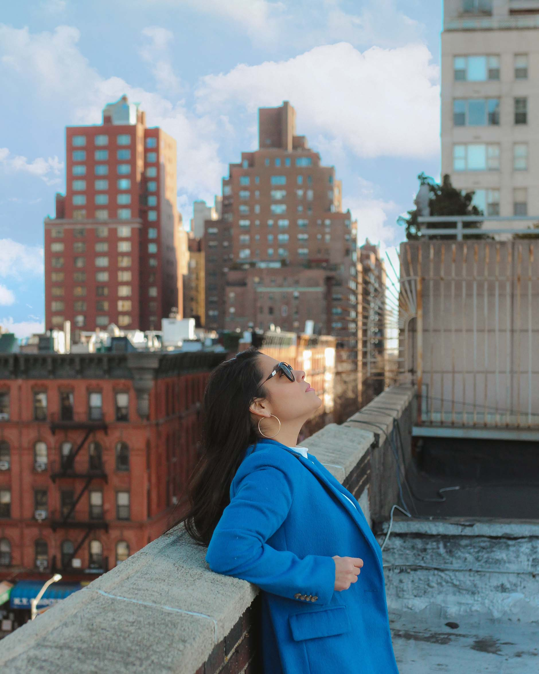 naty michele wearing a blue coat on a new york city rooftop