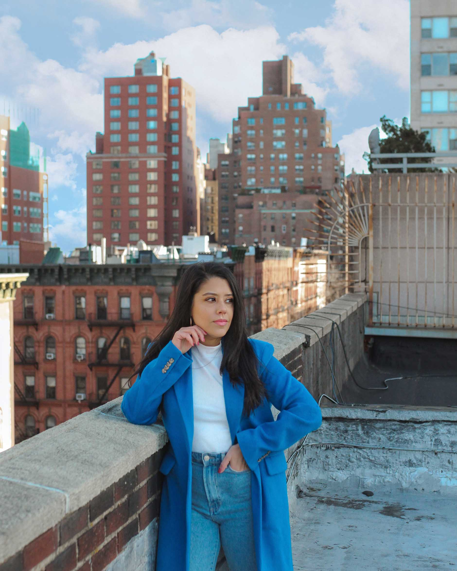 naty michele in a blue coat on a new york city rooftop
