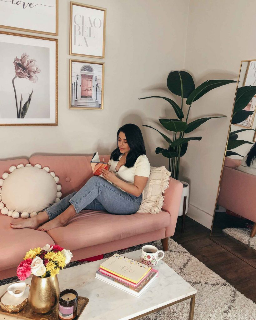 living room decor with a faux plant and large gold mirror, naty michele is on the sofa journaling