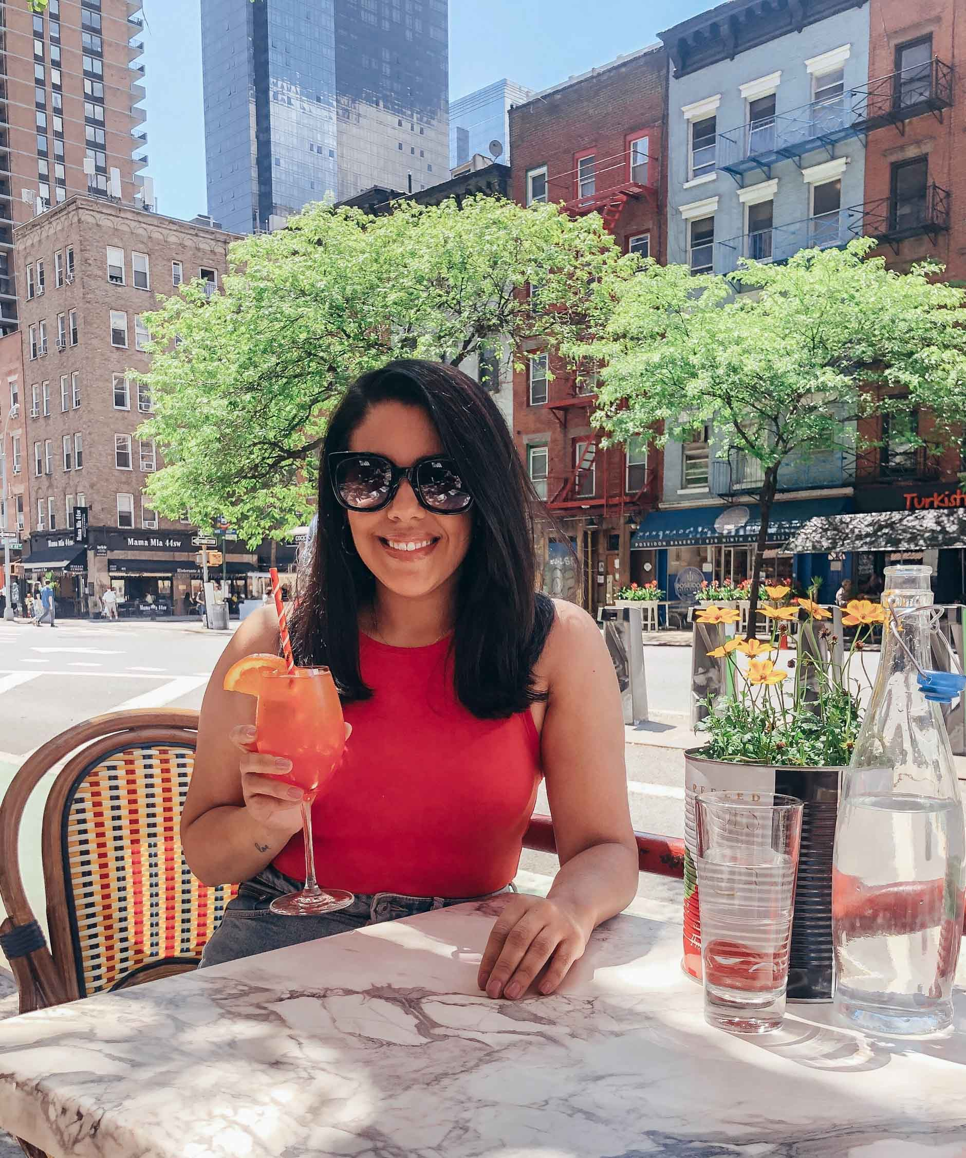 naty michele in nyc with an aperol spritz on a solo date